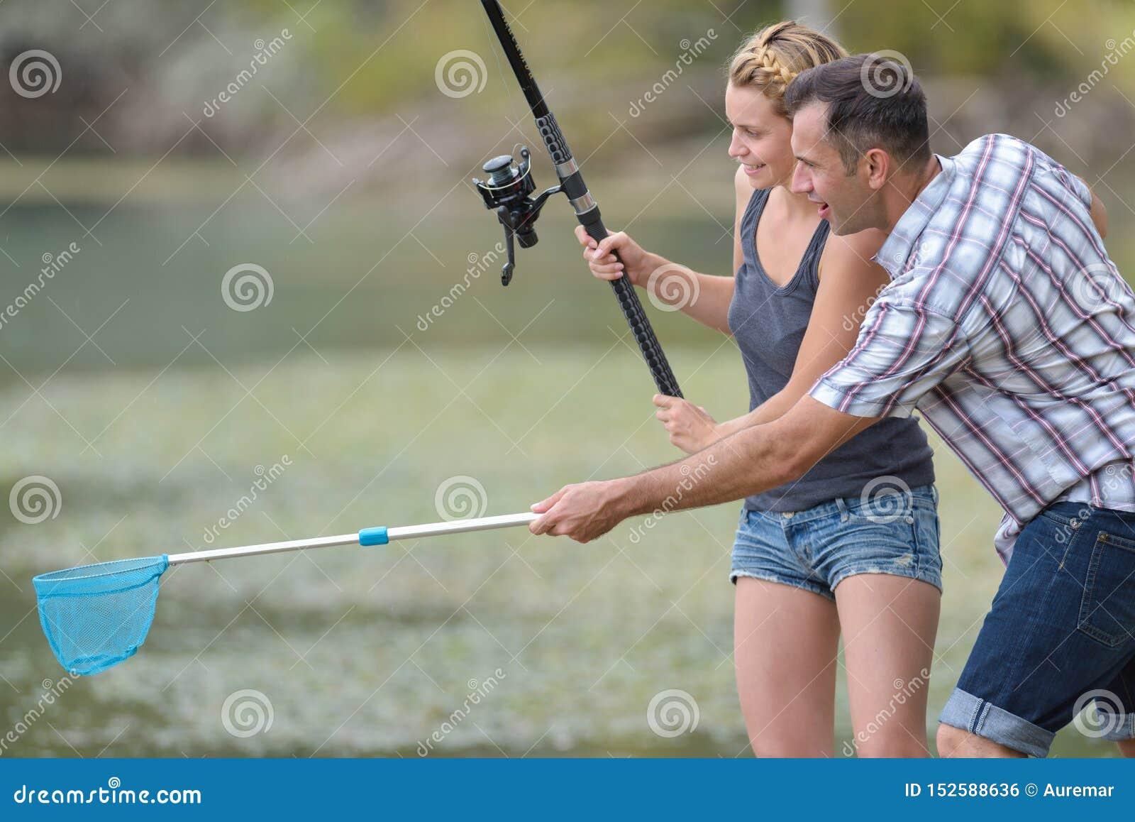 Hombre con la novia de la demostración de la caña de pescar cómo pescar