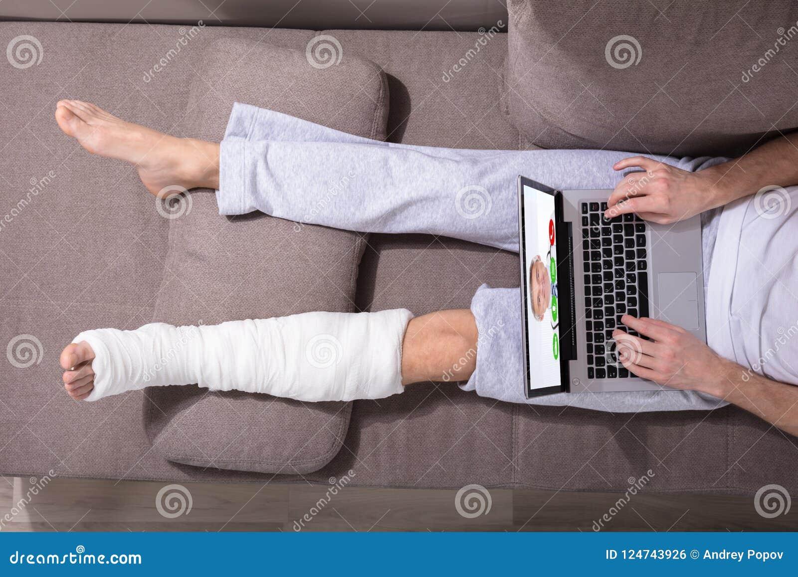 Hombre con la pierna enyesada usando el ordenador portátil