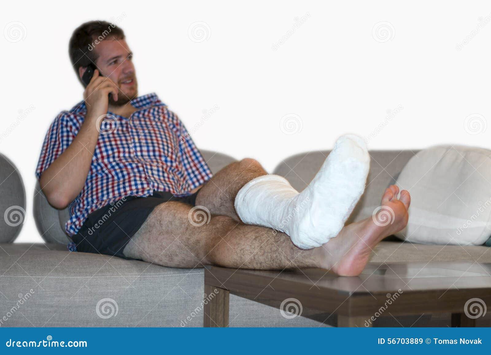 Hombre con la pierna fracturada que se sienta en Sofa Talking On Cellphone