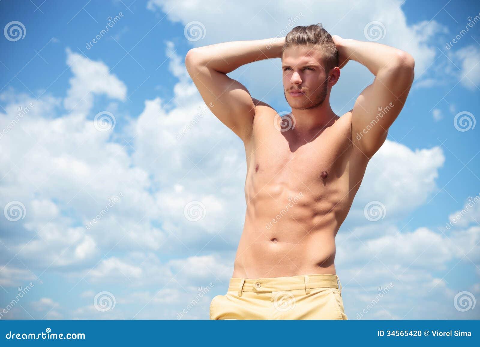 Hombre con las tetas al aire al aire libre con las manos en la parte posterior de la cabeza