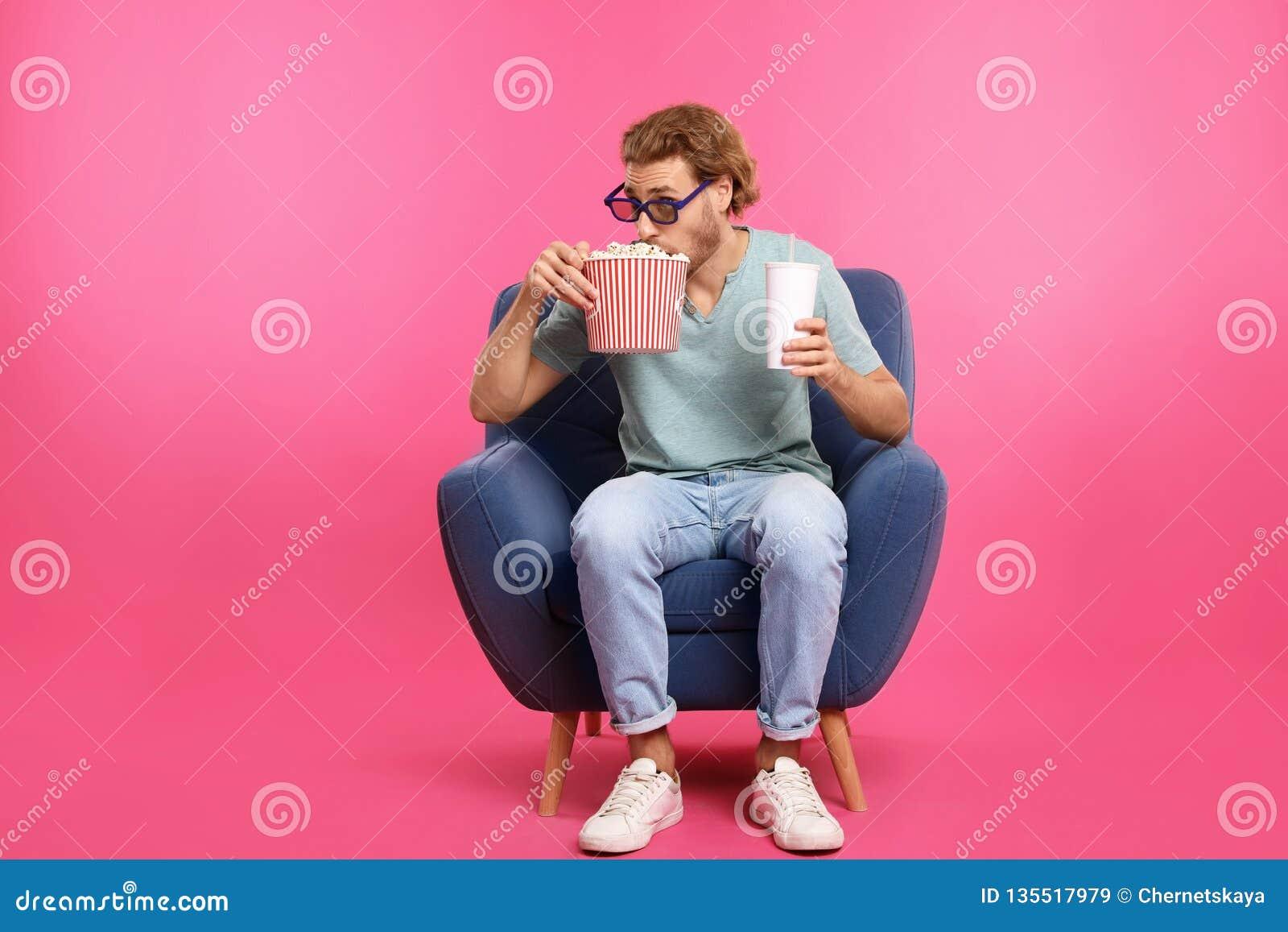 Hombre con los vidrios 3D, las palomitas y la bebida sentándose en butaca durante la demostración del cine