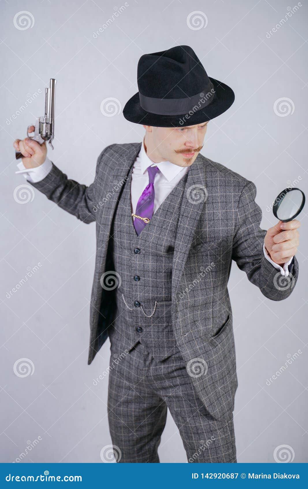 Hombre con un bigote vestido en un traje de la tela escocesa del negocio con un lazo, reteniendo una lupa y un arma en un estudio