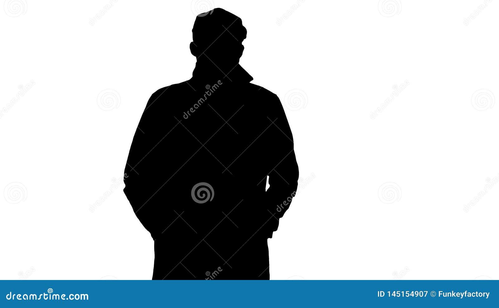 Hombre confiado de la silueta en el foso que lleva a cabo las manos en los bolsillos y caminar