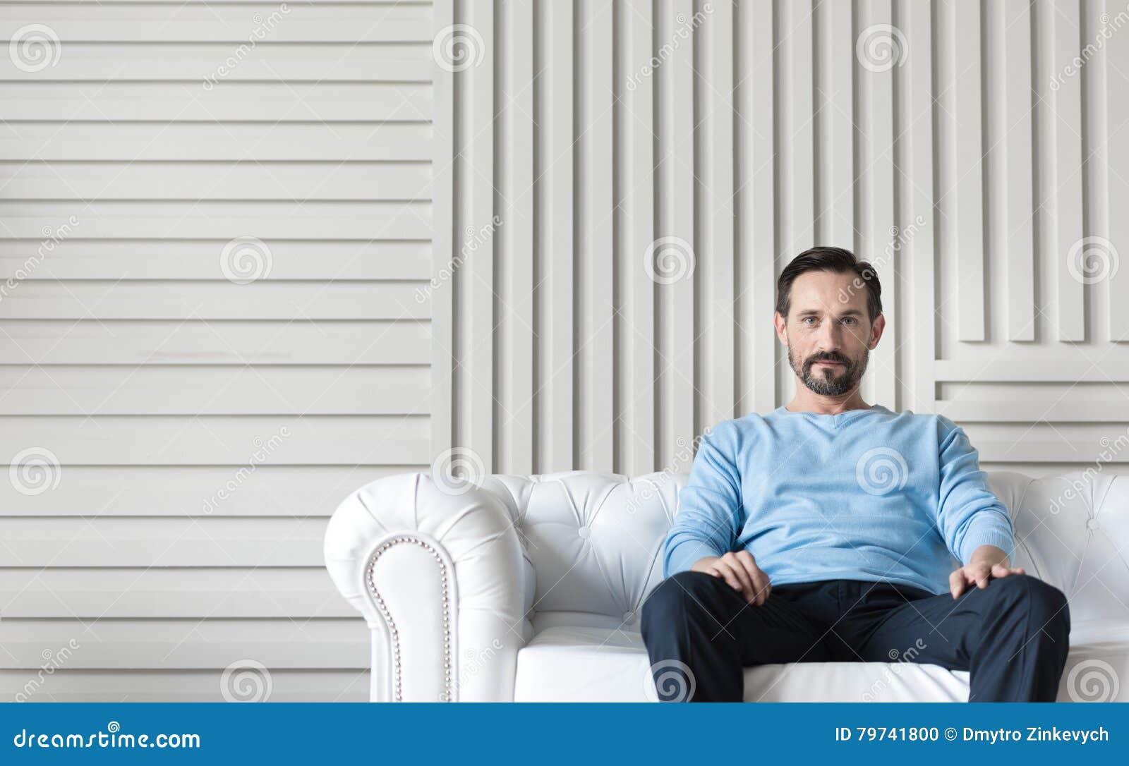 Hombre confiado hermoso que se sienta en el medio del sofá