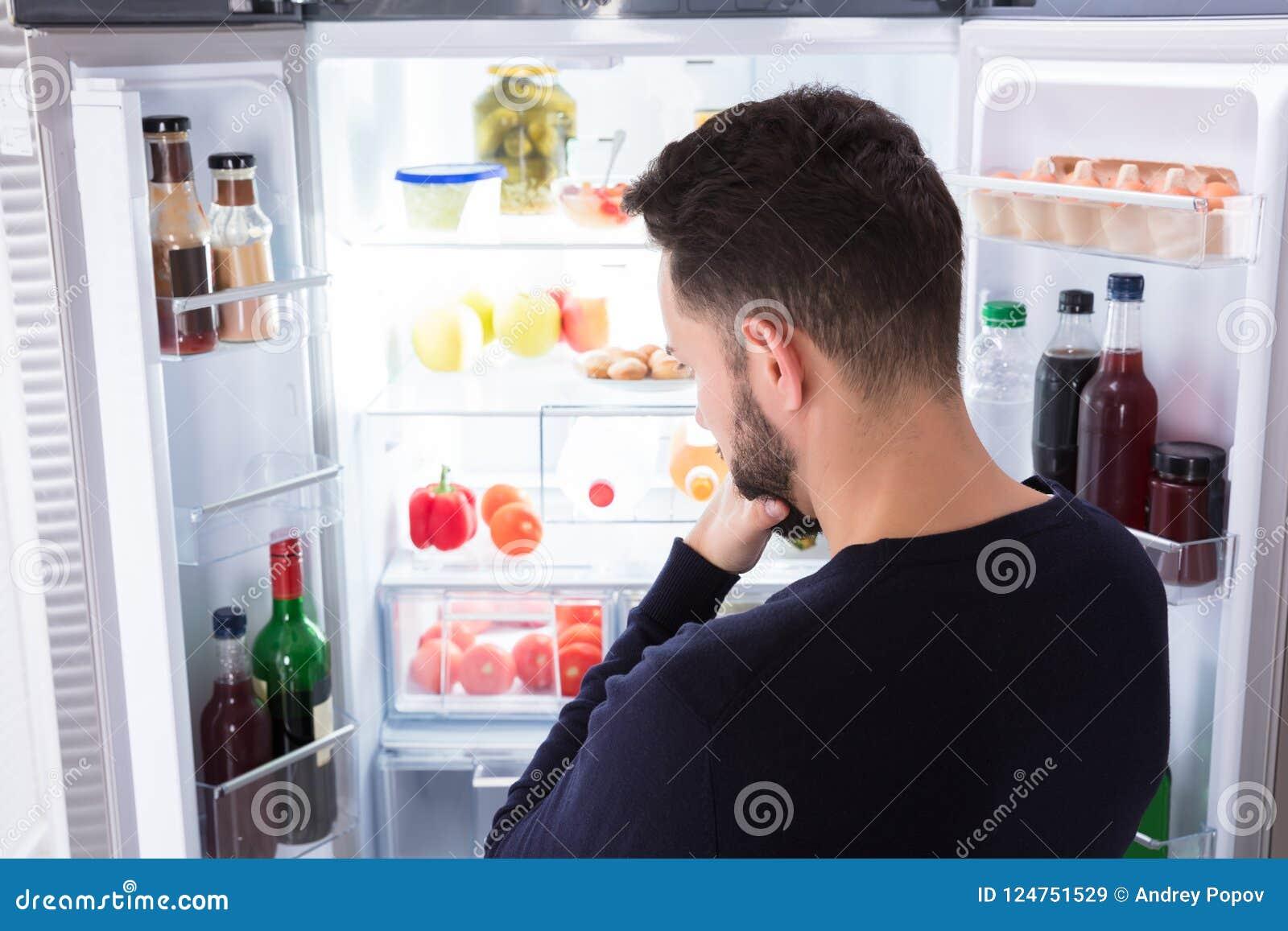 Hombre confuso que mira la comida en refrigerador