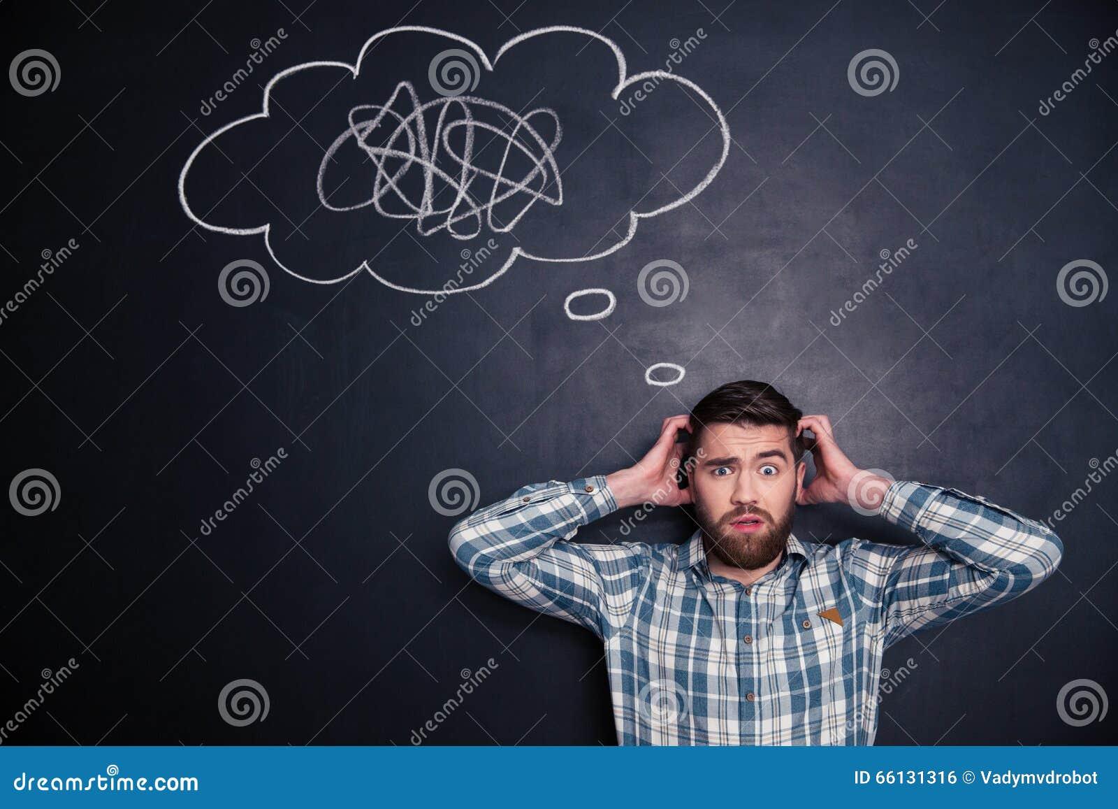 Hombre confuso que piensa en problema con el tablero negro detrás de él