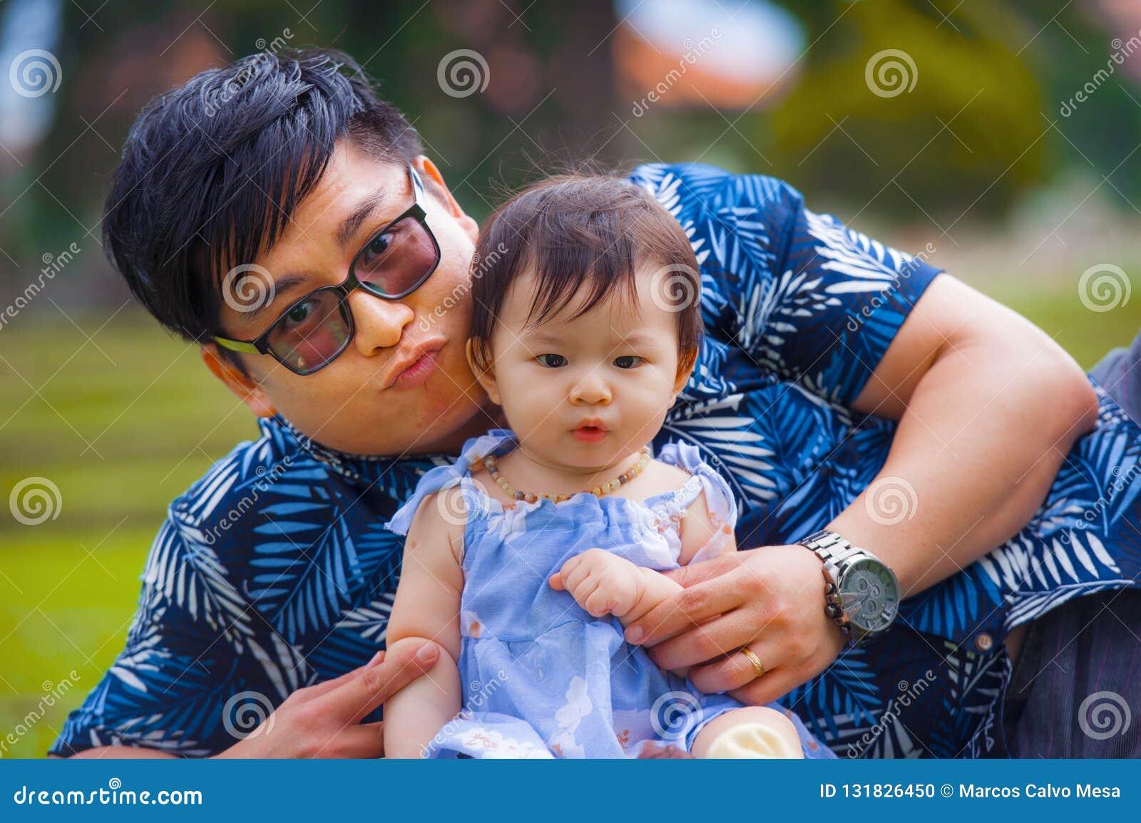 Hombre coreano asiático juguetón feliz como padre de amor que goza de la hija dulce y hermosa del bebé que sienta junto jugar en