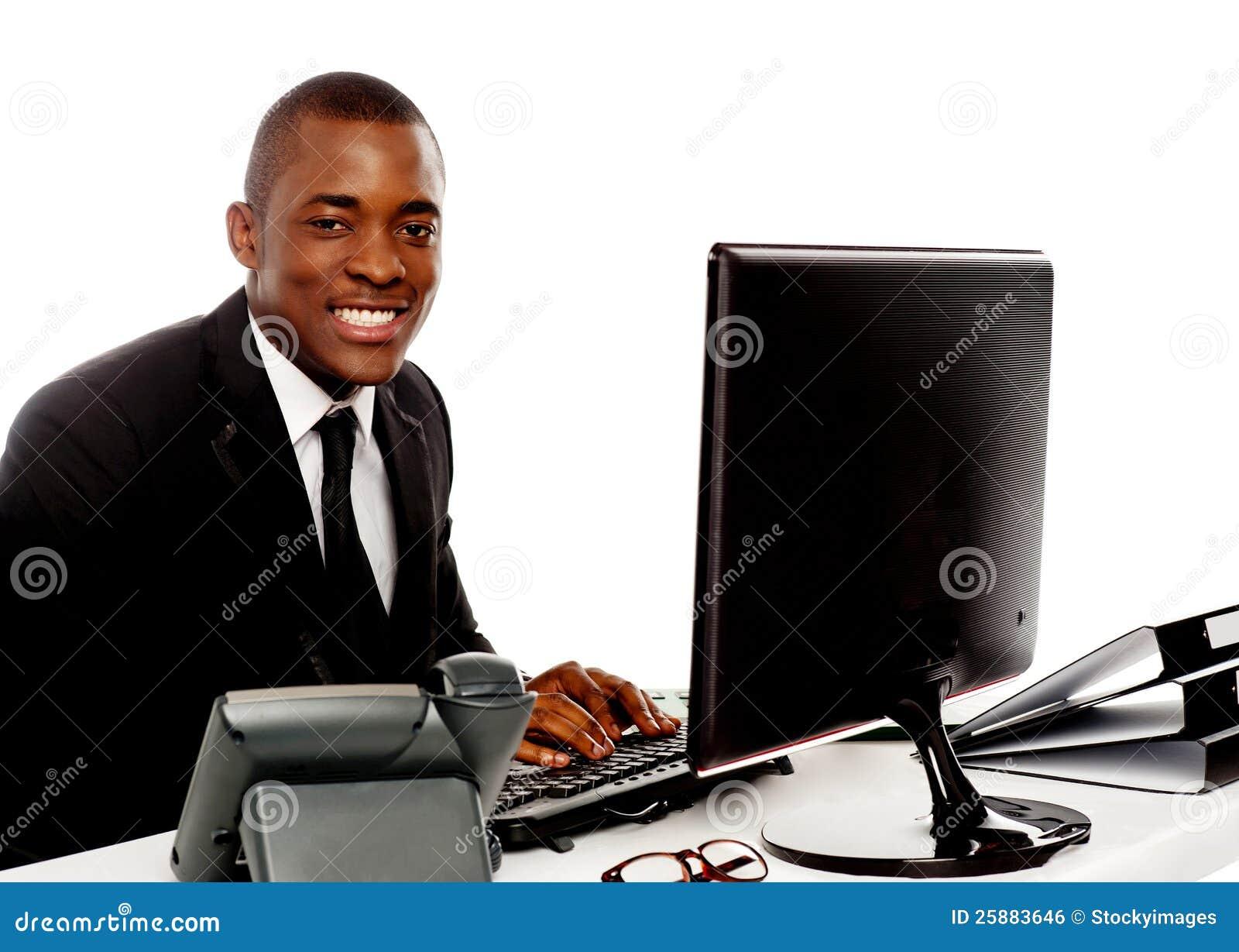 Hombre corporativo joven sonriente que usa el ordenador