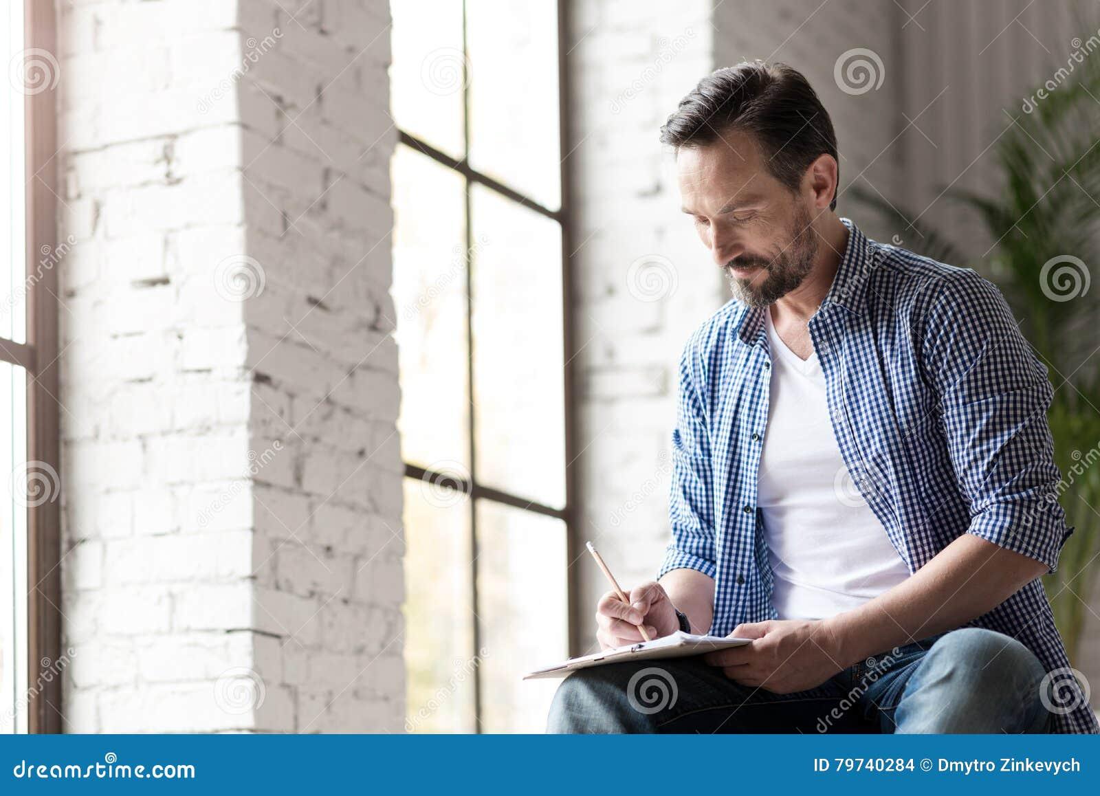 Hombre creativo alegre implicado en el dibujo