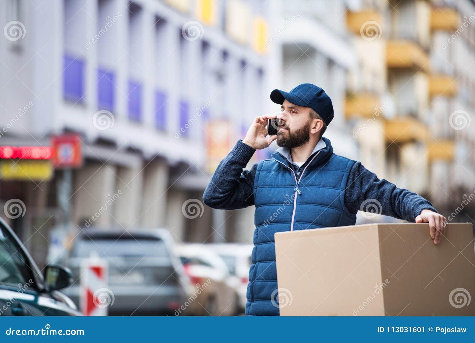 Hombre de entrega con una caja del paquete en la calle