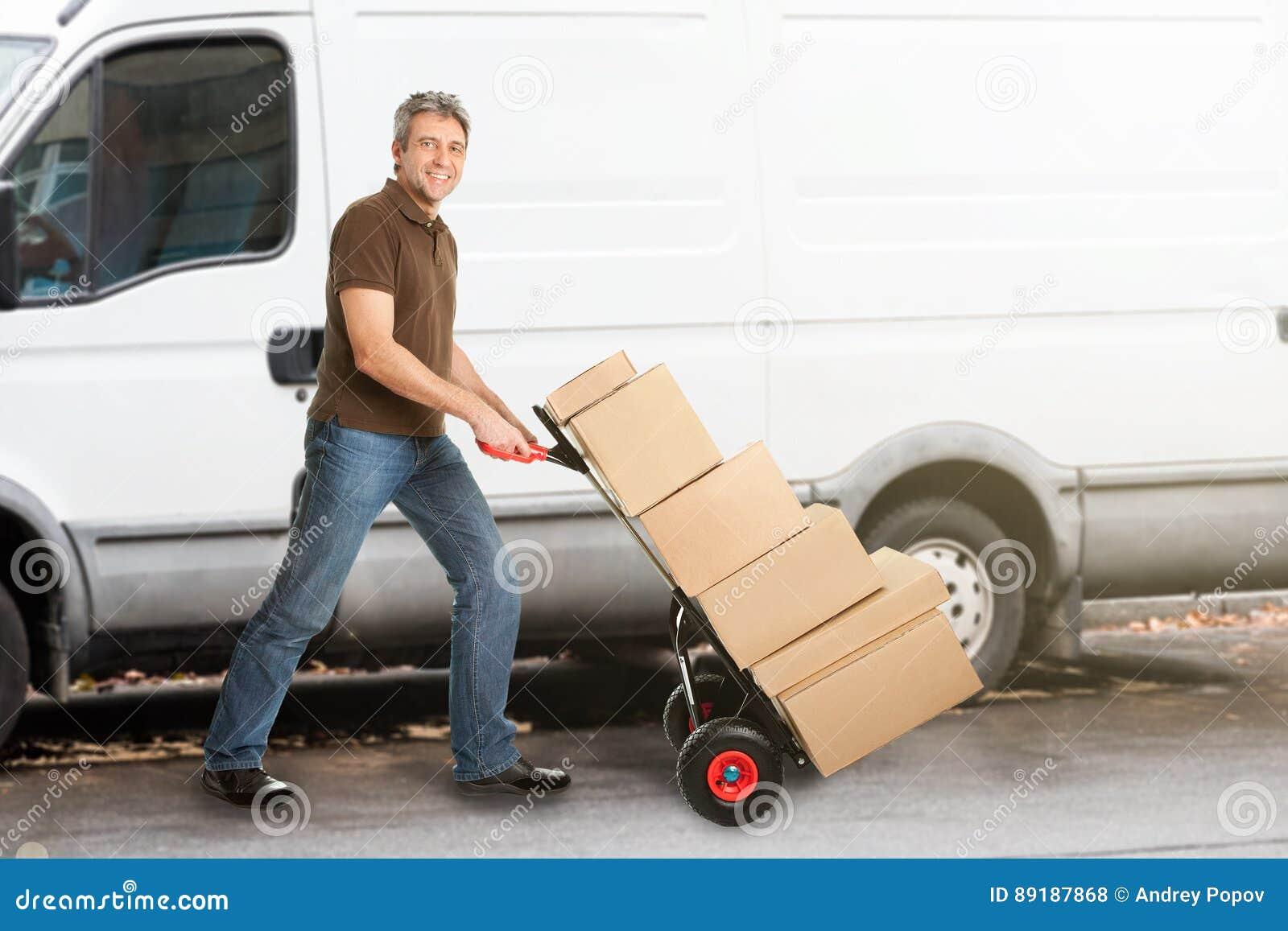 Hombre de entrega que empuja paquetes en Handtruck
