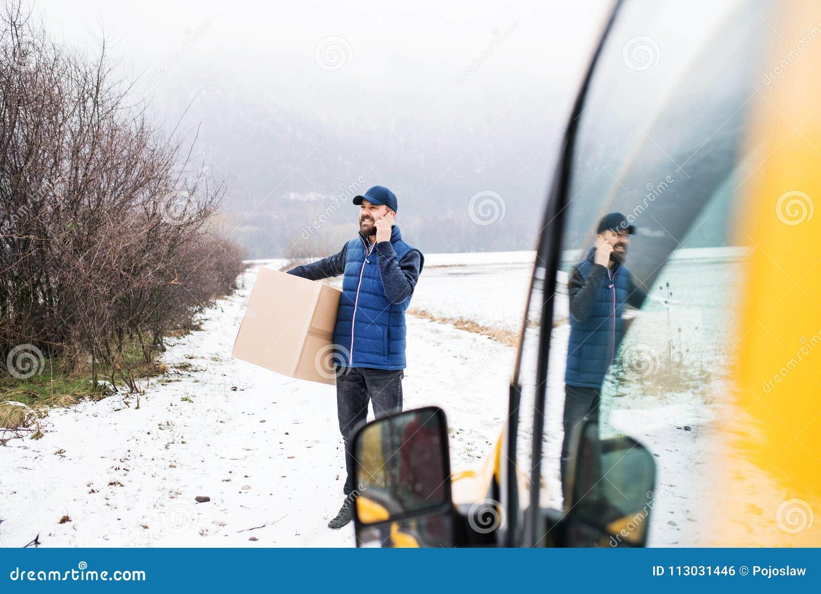 Hombre de entrega que entrega la caja del paquete al beneficiario