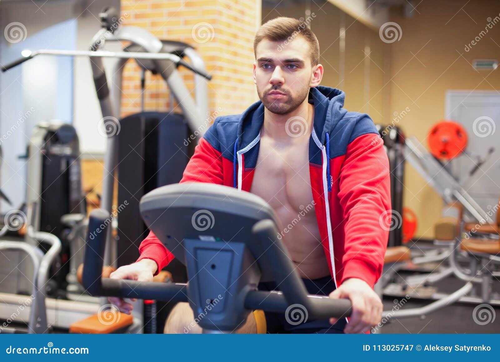 Hombre de la aptitud en la bicicleta que hace el giro en el gimnasio Hombre joven apto que se resuelve en la bici del gimnasio