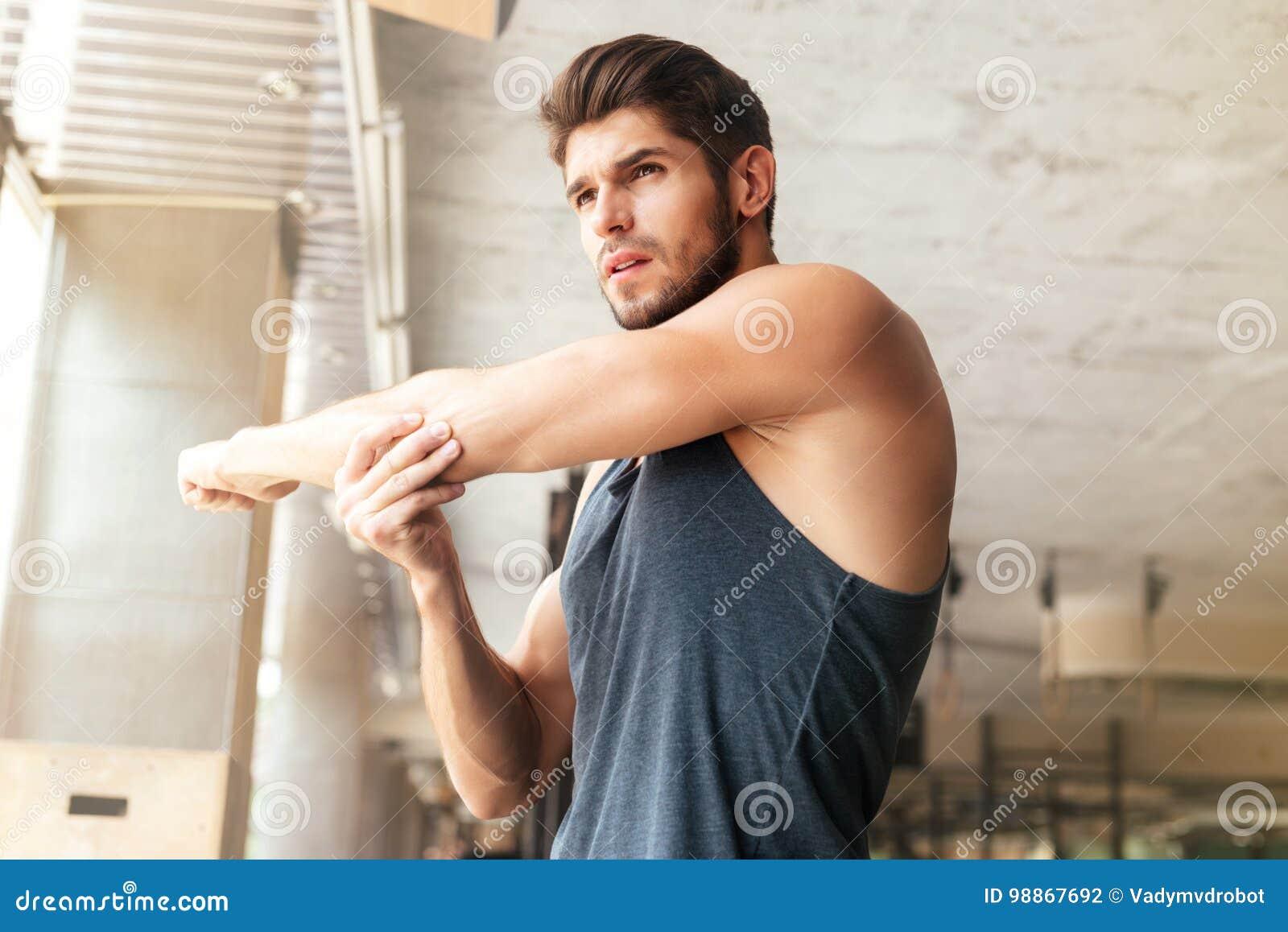 Hombre de la aptitud que calienta en gimnasio
