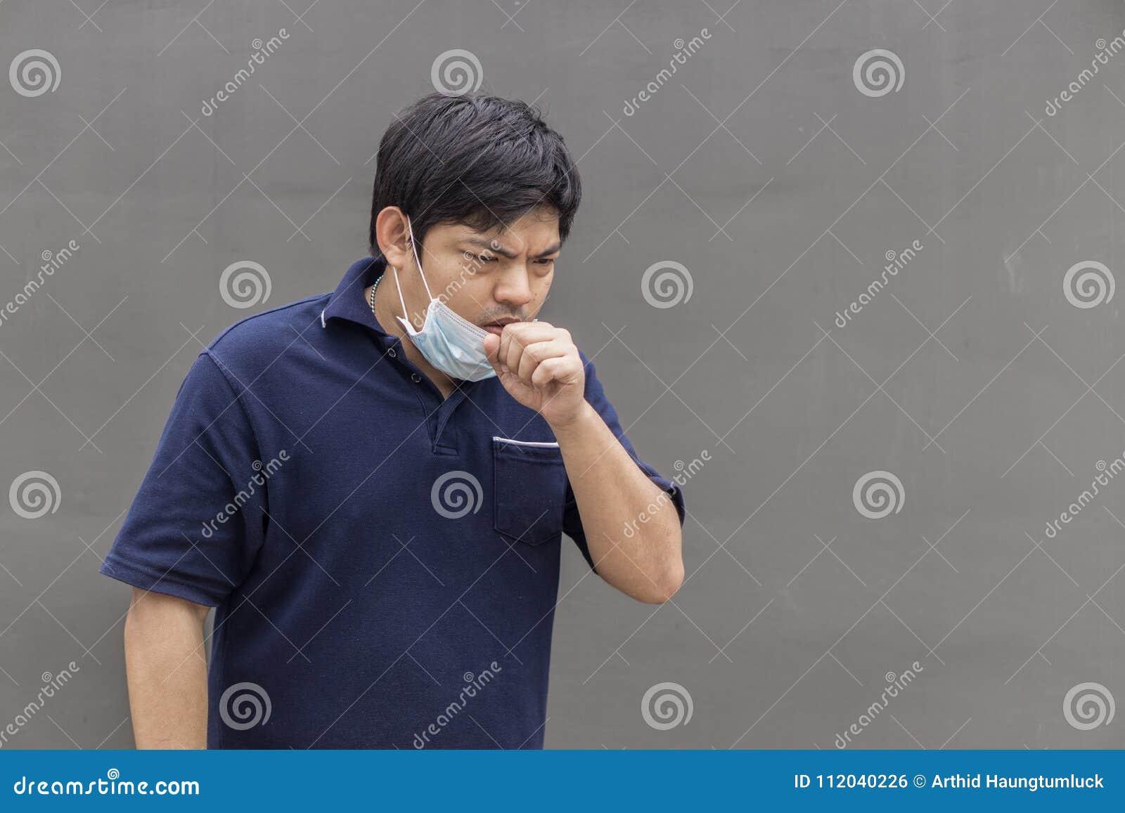 Hombre de la calle asiático que lleva máscaras protectoras , Hombre enfermo con la máscara que lleva de la gripe y nariz que sopl