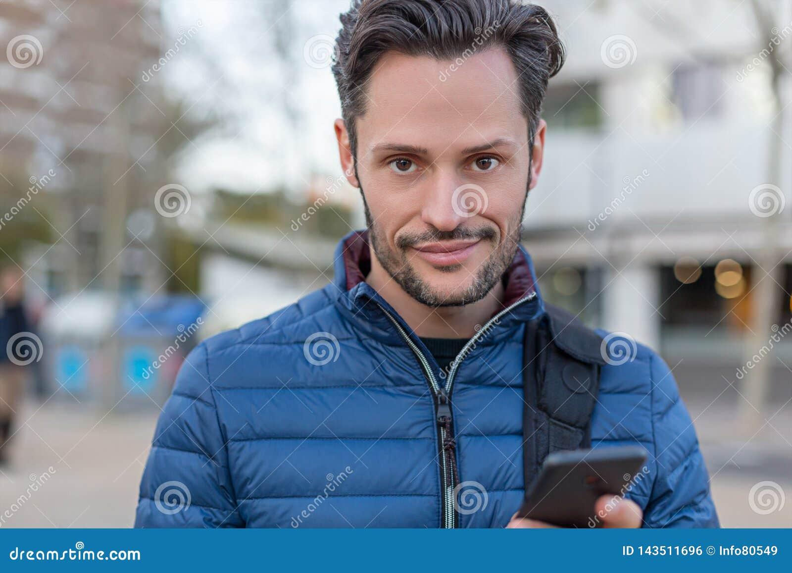 Hombre de la calle sonriente del negocio joven con un teléfono móvil y una chaqueta azul