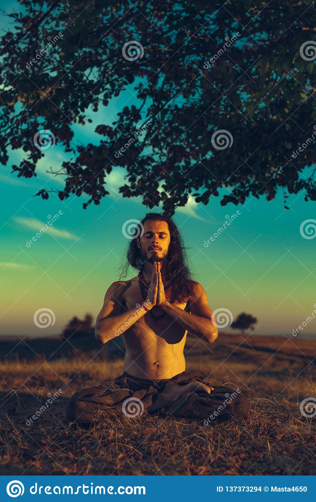 Hombre de la yogui que medita en la puesta del sol en las colinas Armonía emocional de la espiritualidad del concepto de la relaj