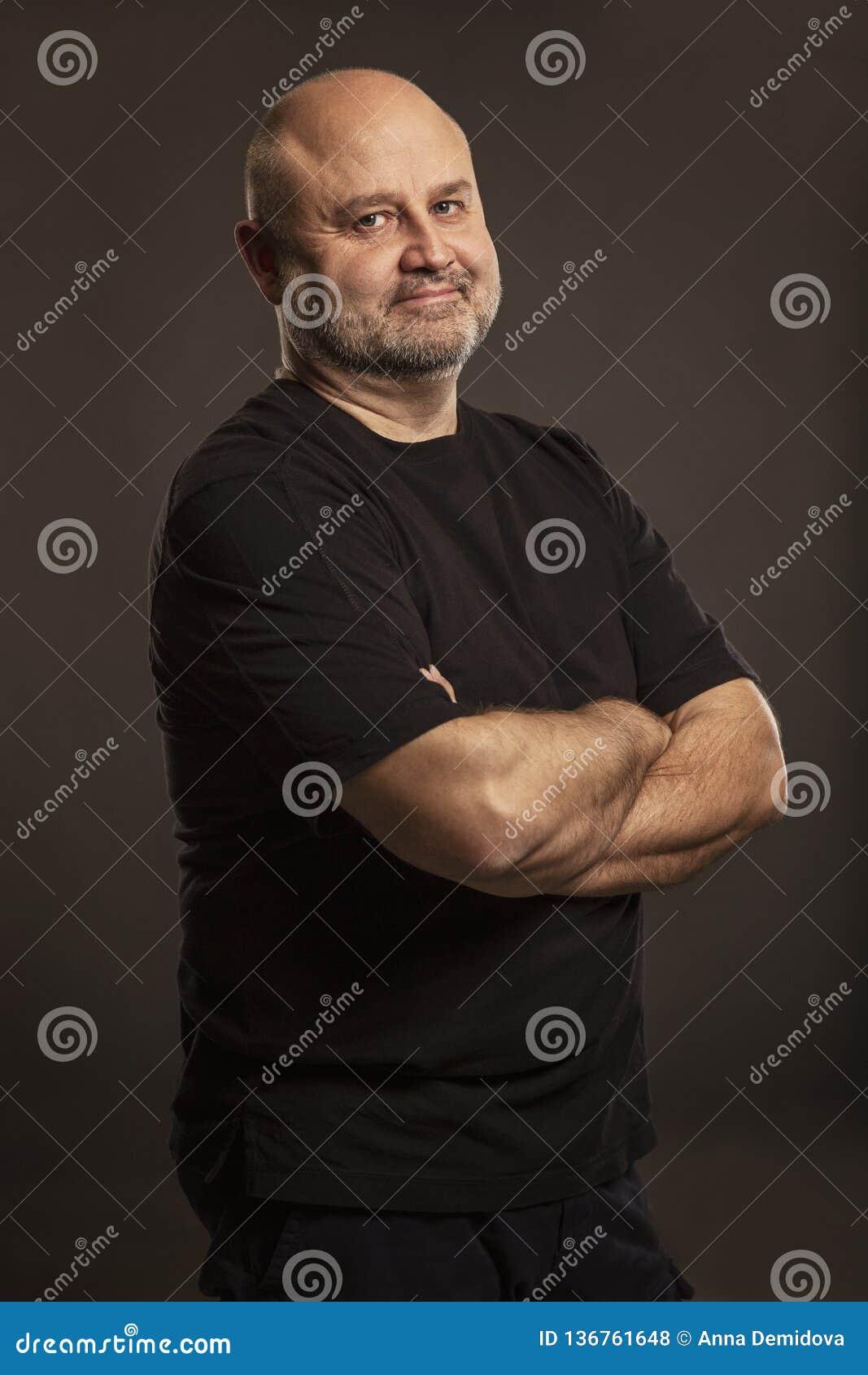 Hombre de mediana edad calvo, fondo oscuro