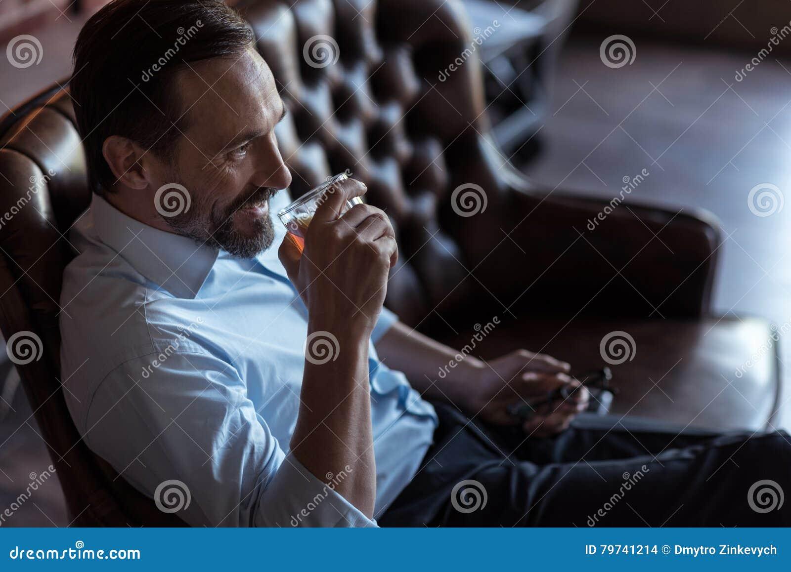 Hombre de negocios acertado alegre que goza el suyo bebida