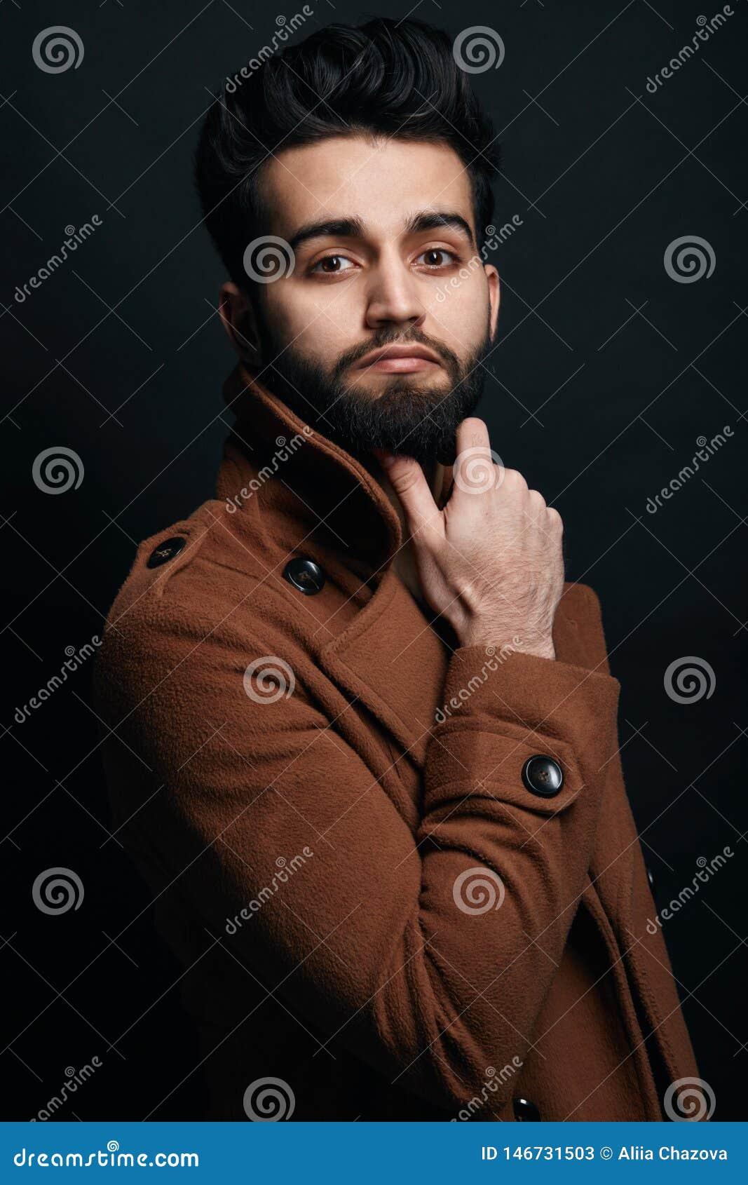 Hombre de negocios acertado confiado en capa marrón