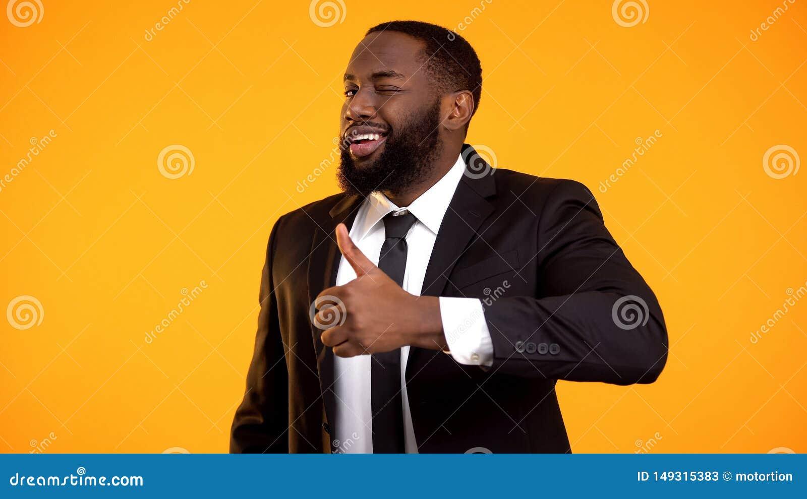 Hombre de negocios afroamericano confiado en el traje que hace los pulgares-para arriba y que gui?a, anuncio