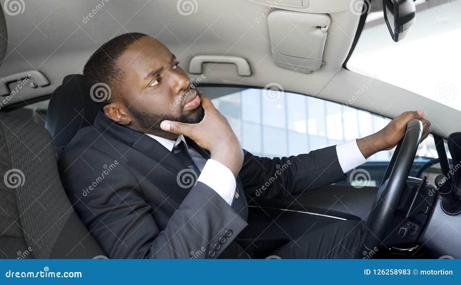 Hombre de negocios afroamericano hermoso que mira en espejo de coche, teniendo dudas