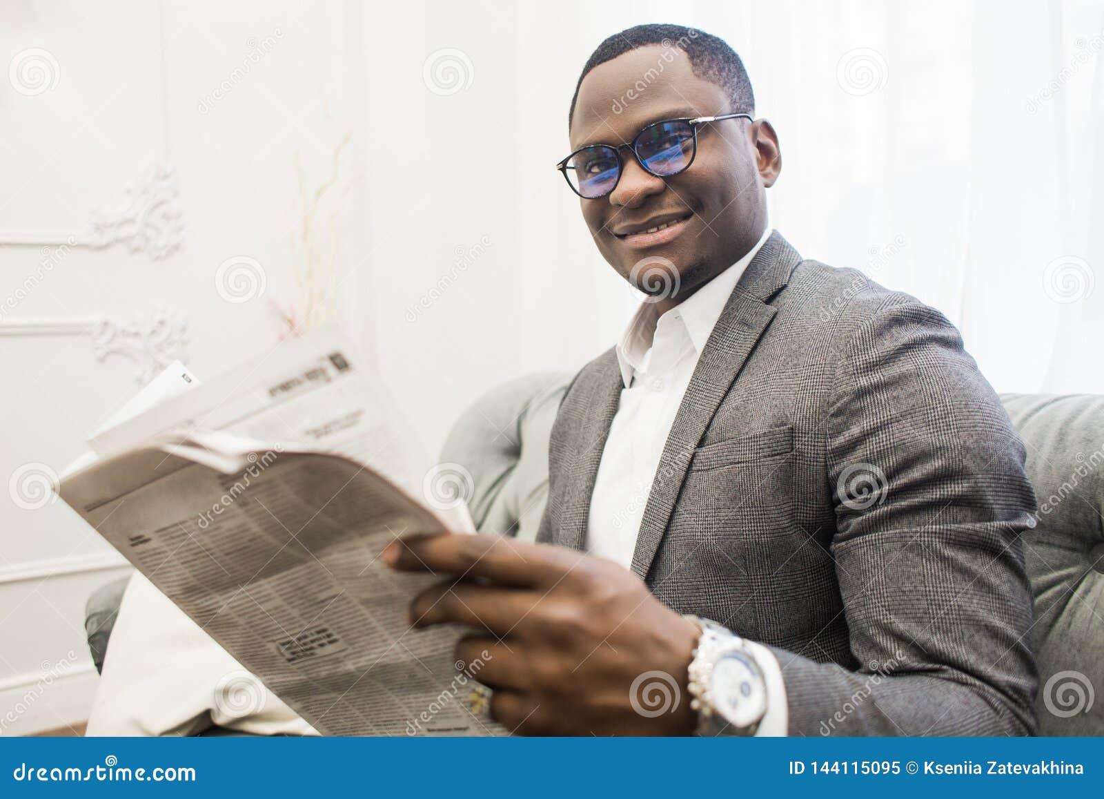 Hombre de negocios afroamericano joven en un traje gris que lee un periódico mientras que se sienta en un sofá