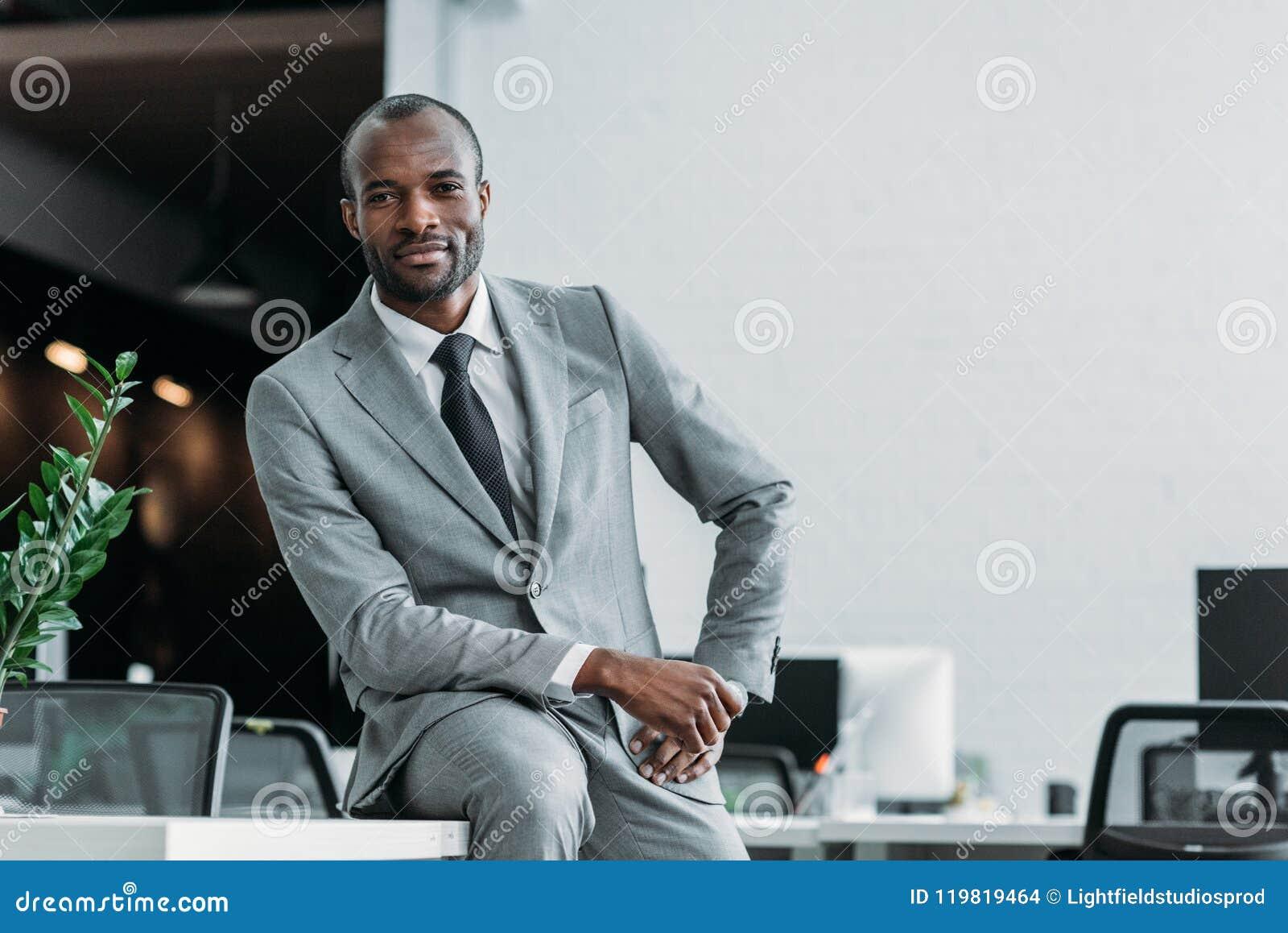 Hombre de negocios afroamericano que se sienta en la tabla