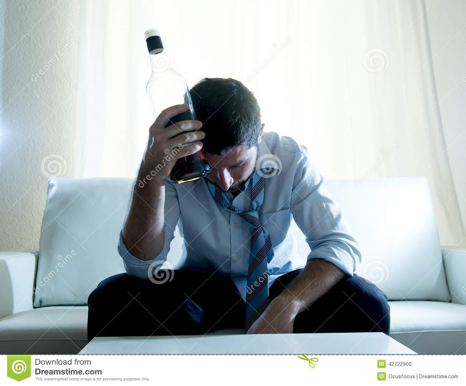 Hombre de negocios alcohólico que lleva el lazo flojo azul bebido con la botella de whisky en el sofá