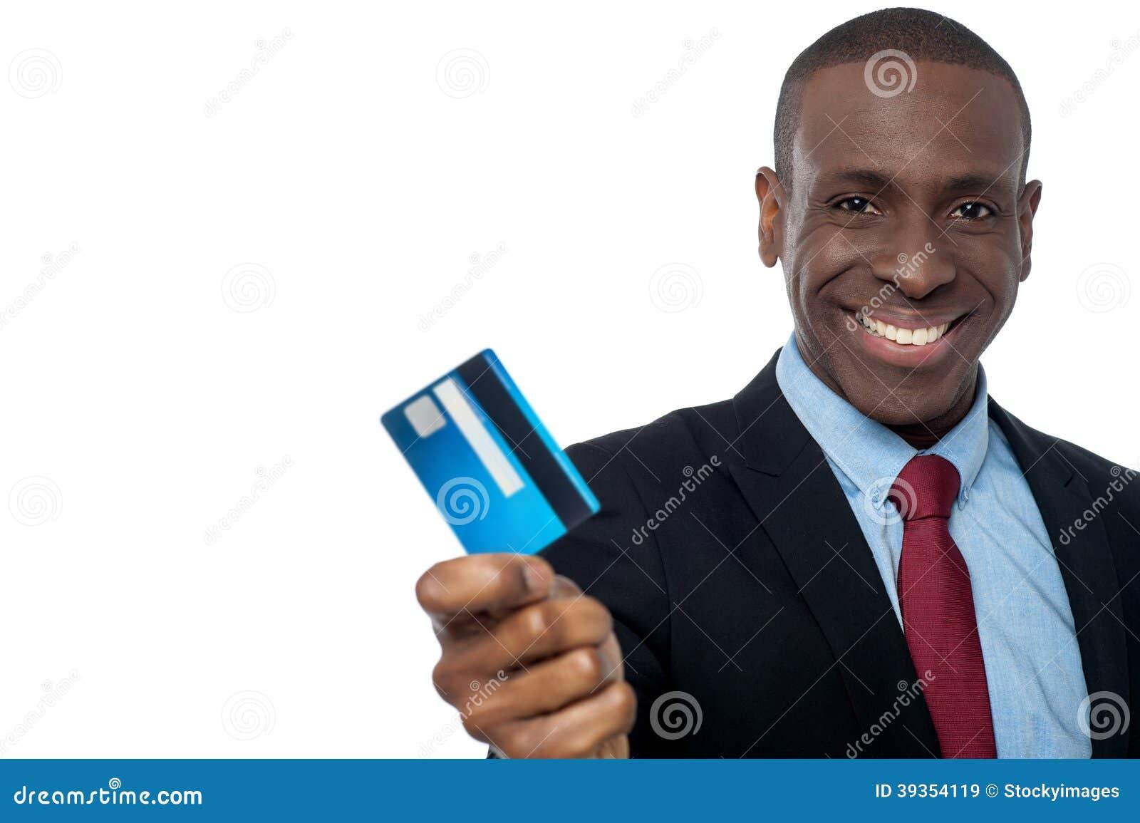 Hombre de negocios alegre que sostiene la tarjeta de crédito