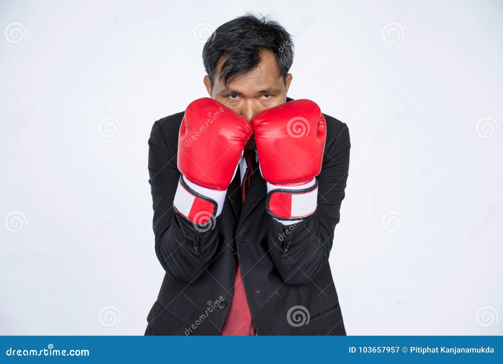 Hombre de negocios asiático con el guante de boxeo rojo en el fondo blanco