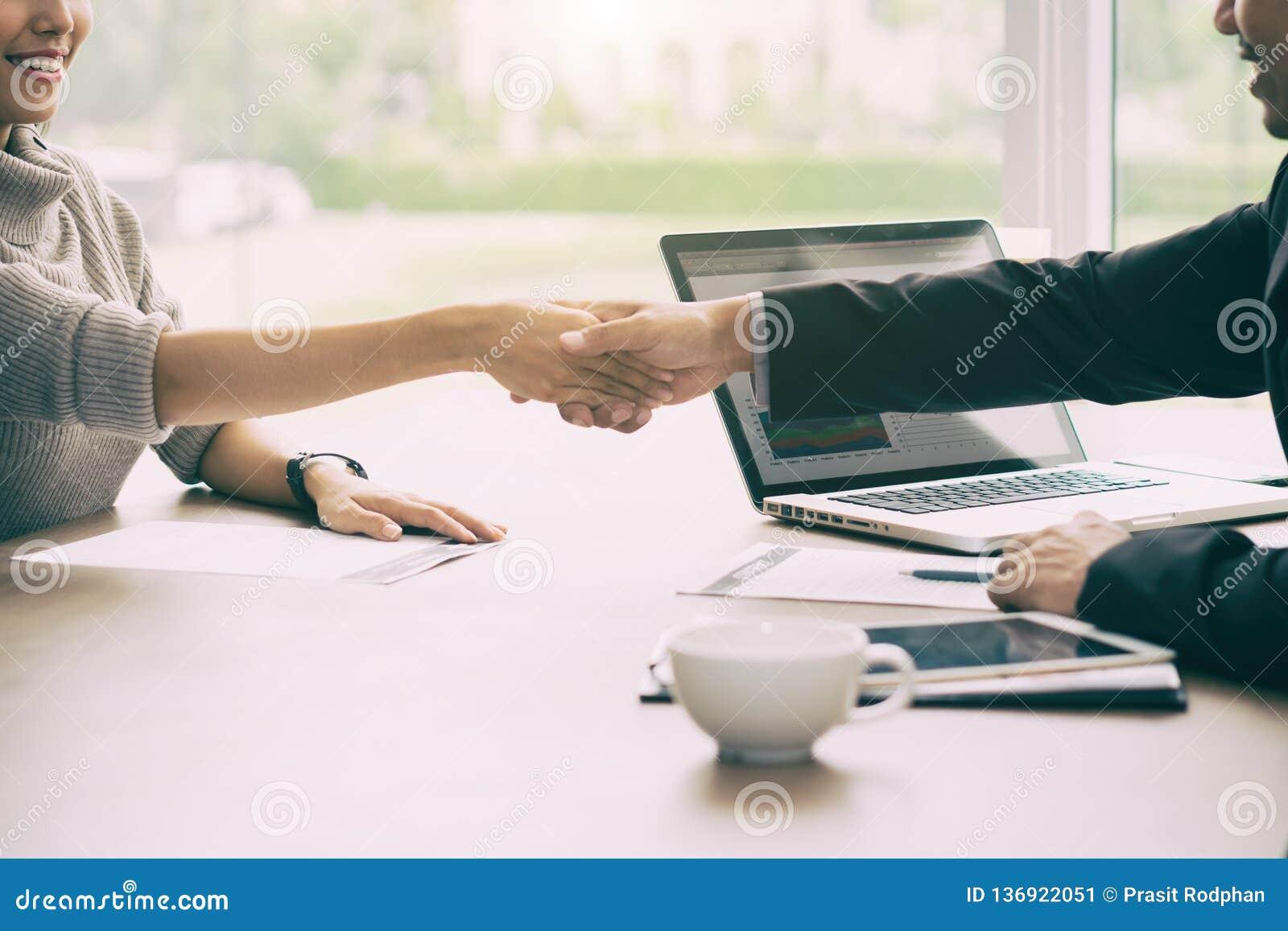 Hombre de negocios asiático y empresaria del trabajo acertado que sacuden las manos en sala de juntas al acabar para arriba una r