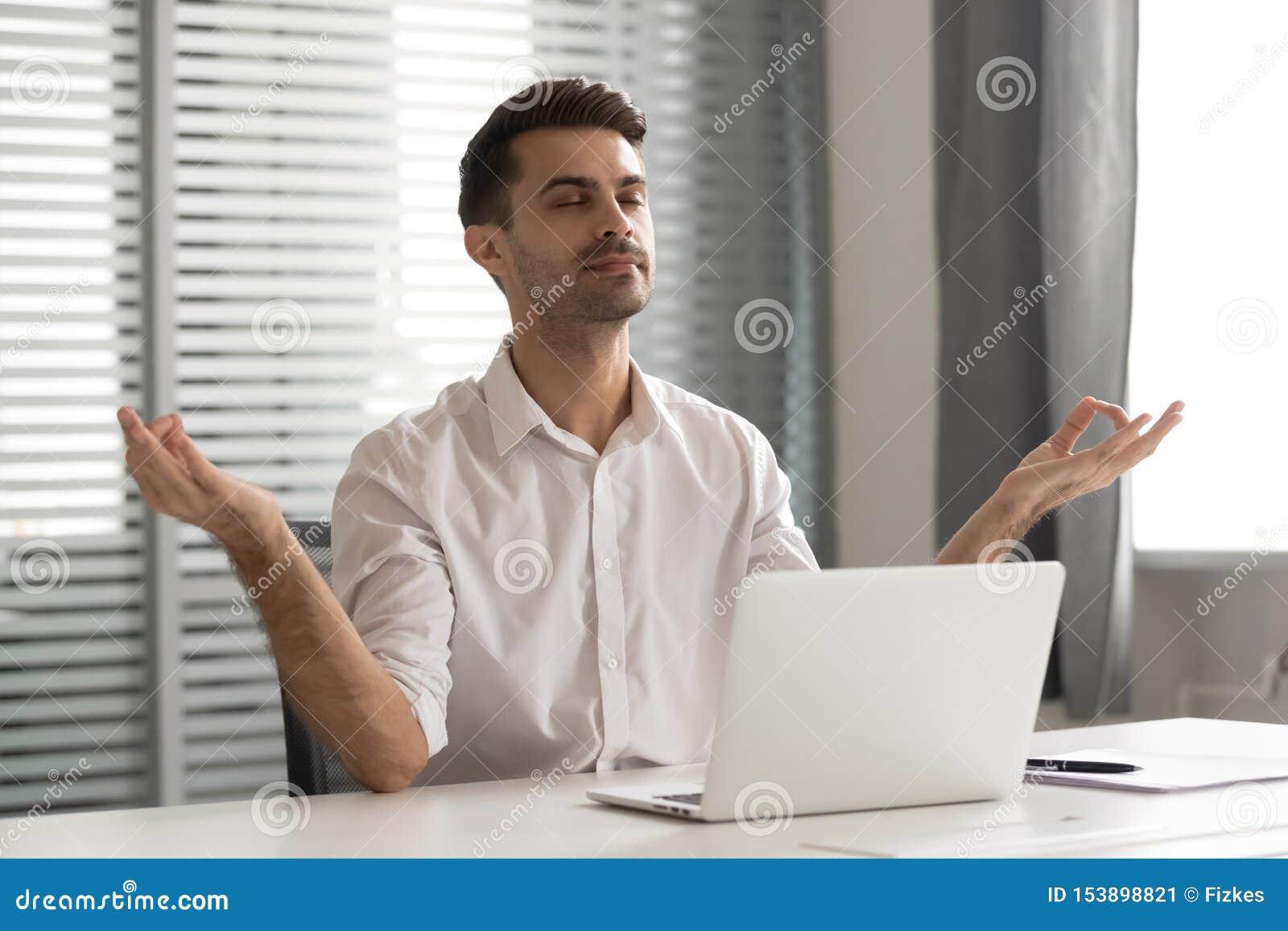 Hombre de negocios atento tranquilo que toma la rotura para meditar para sentarse en el escritorio de oficina