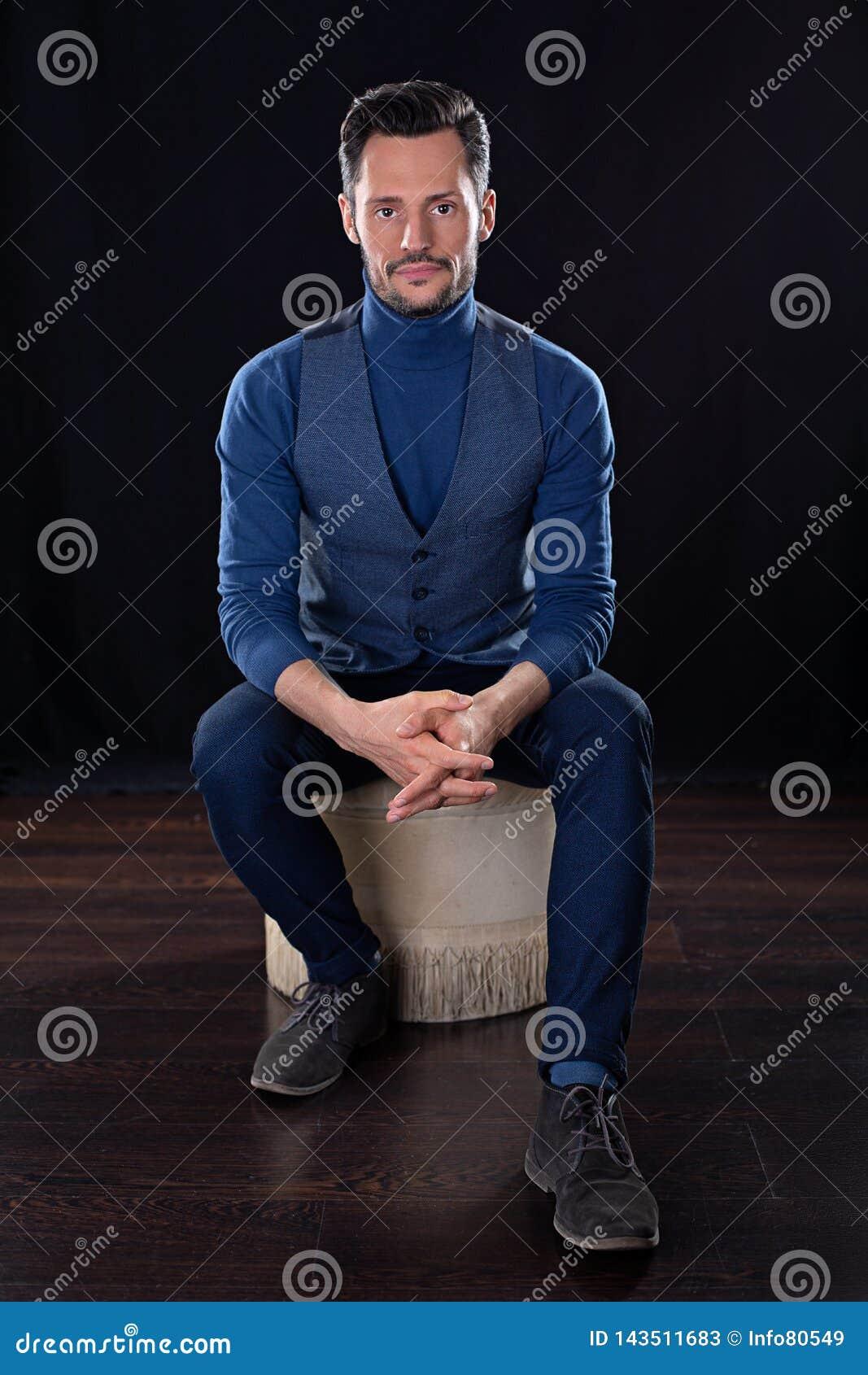 Hombre de negocios atractivo joven, sentándose con las manos cruzadas