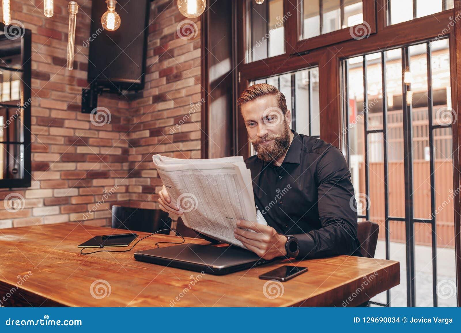 Hombre de negocios barbudo joven que lee un periódico