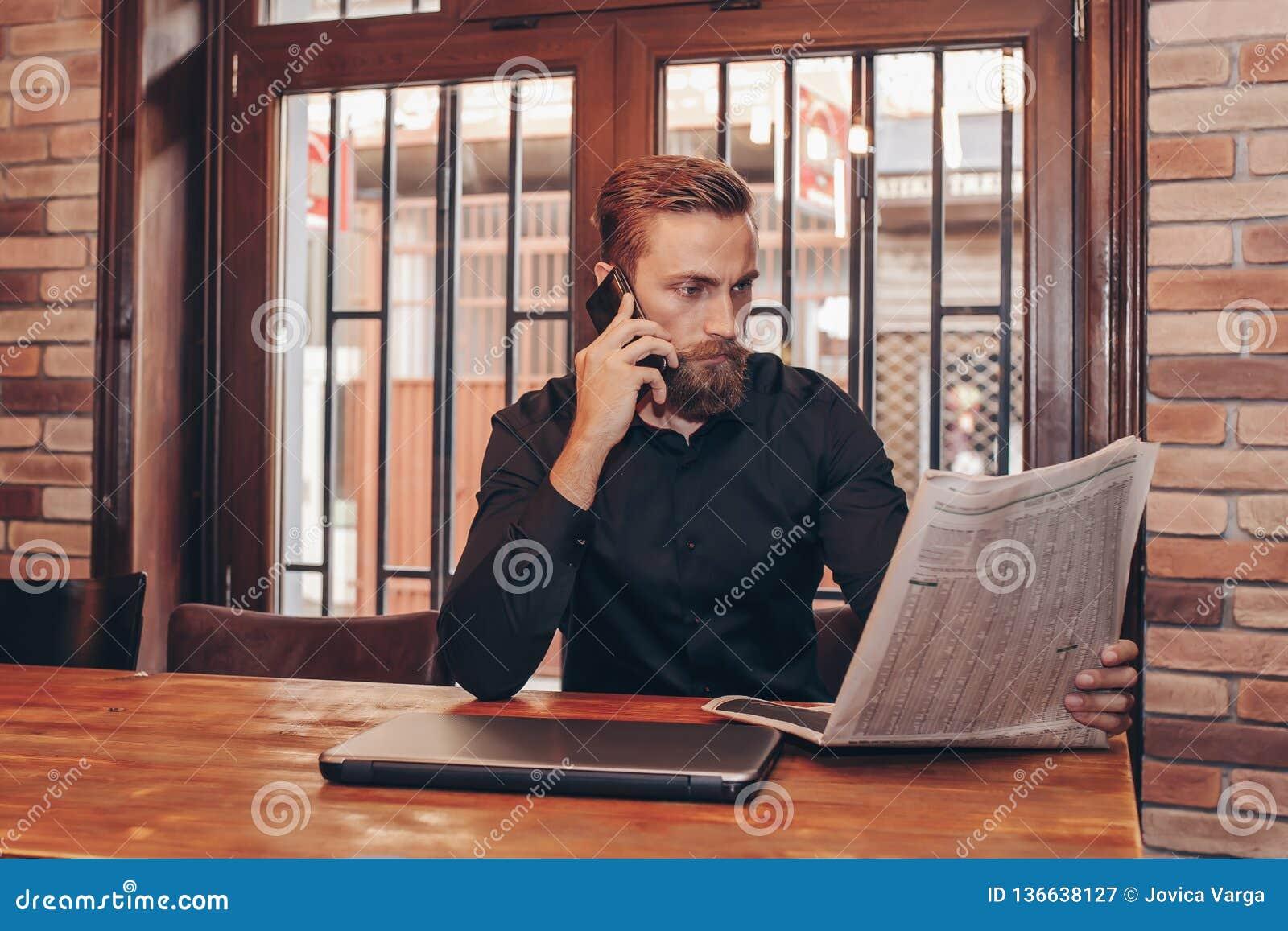Hombre de negocios barbudo que lee un periódico