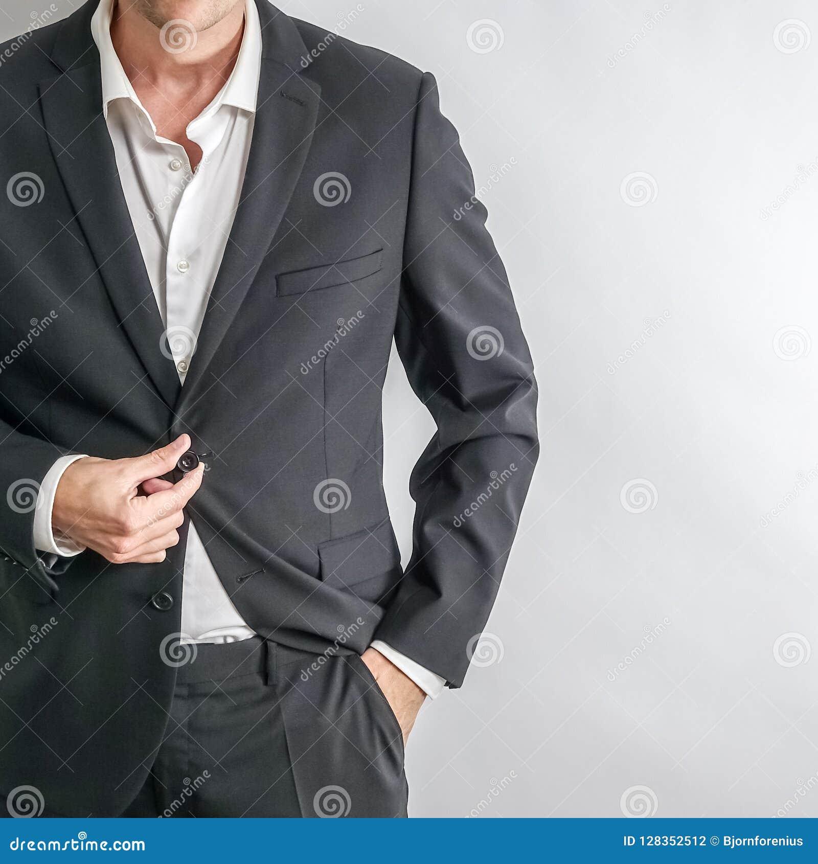 Hombre de negocios bien vestido en el traje negro que ajusta su chaqueta