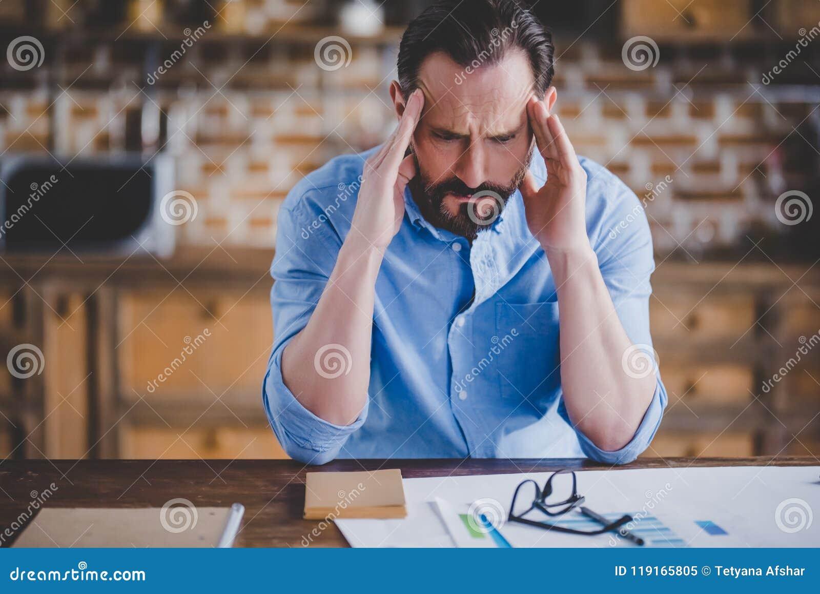 Hombre de negocios cansado con jaqueca después del trabajo