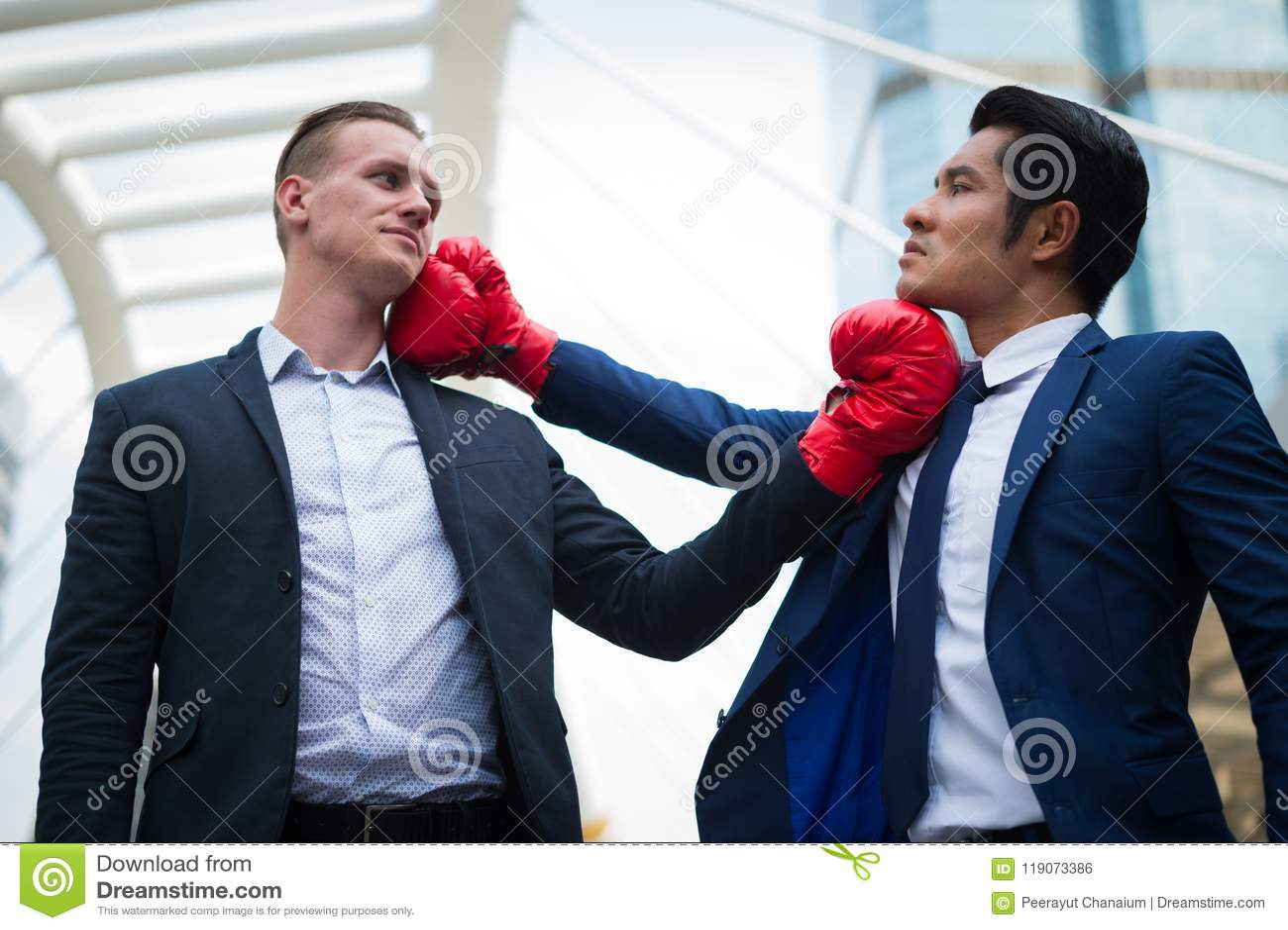 Hombre de negocios caucásico y hombre de negocios asiático con los guantes de boxeo rojos que lucha por gancho a la barbilla Conc
