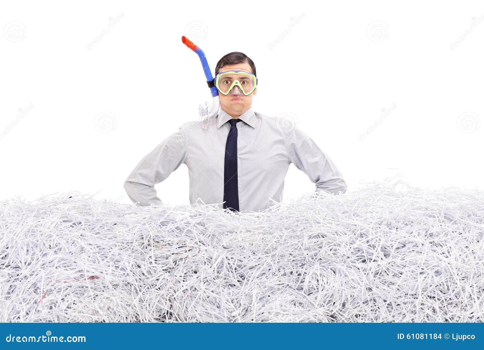 Hombre de negocios con el tubo respirador que se coloca en papel destrozado