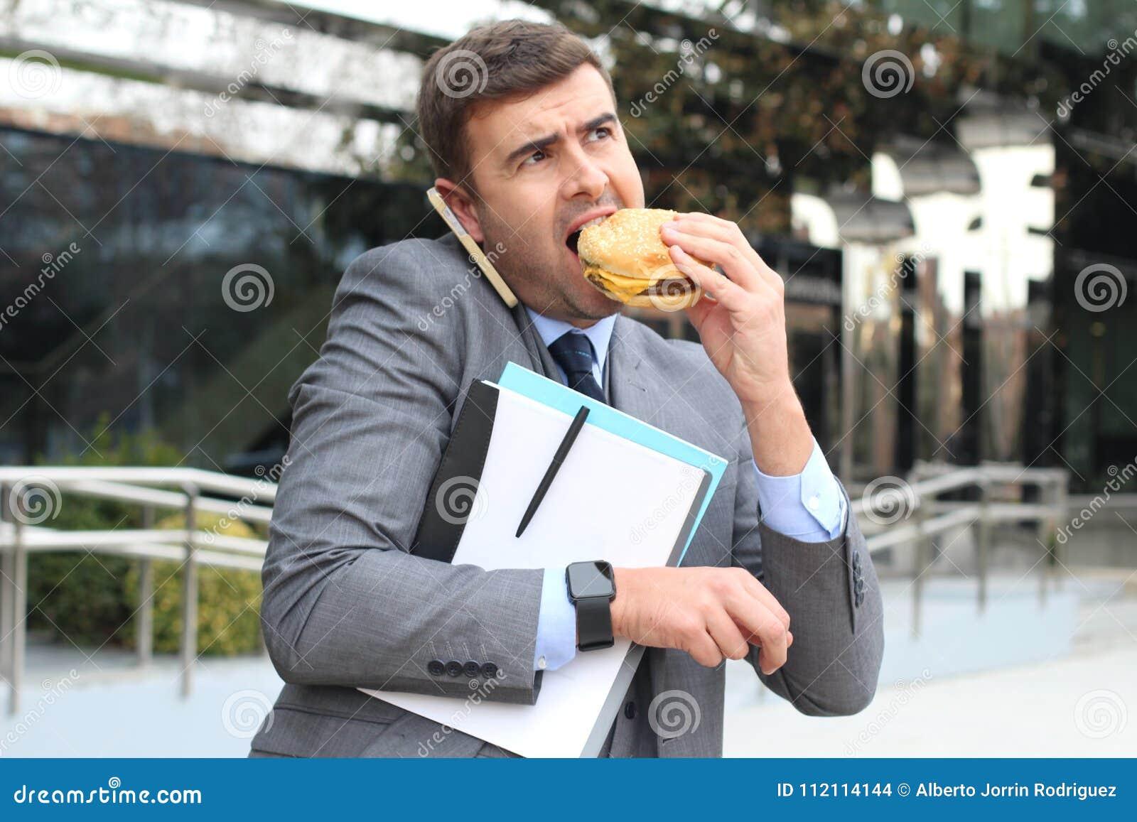 Hombre de negocios con exceso de trabajo que come los alimentos de preparación rápida en camino