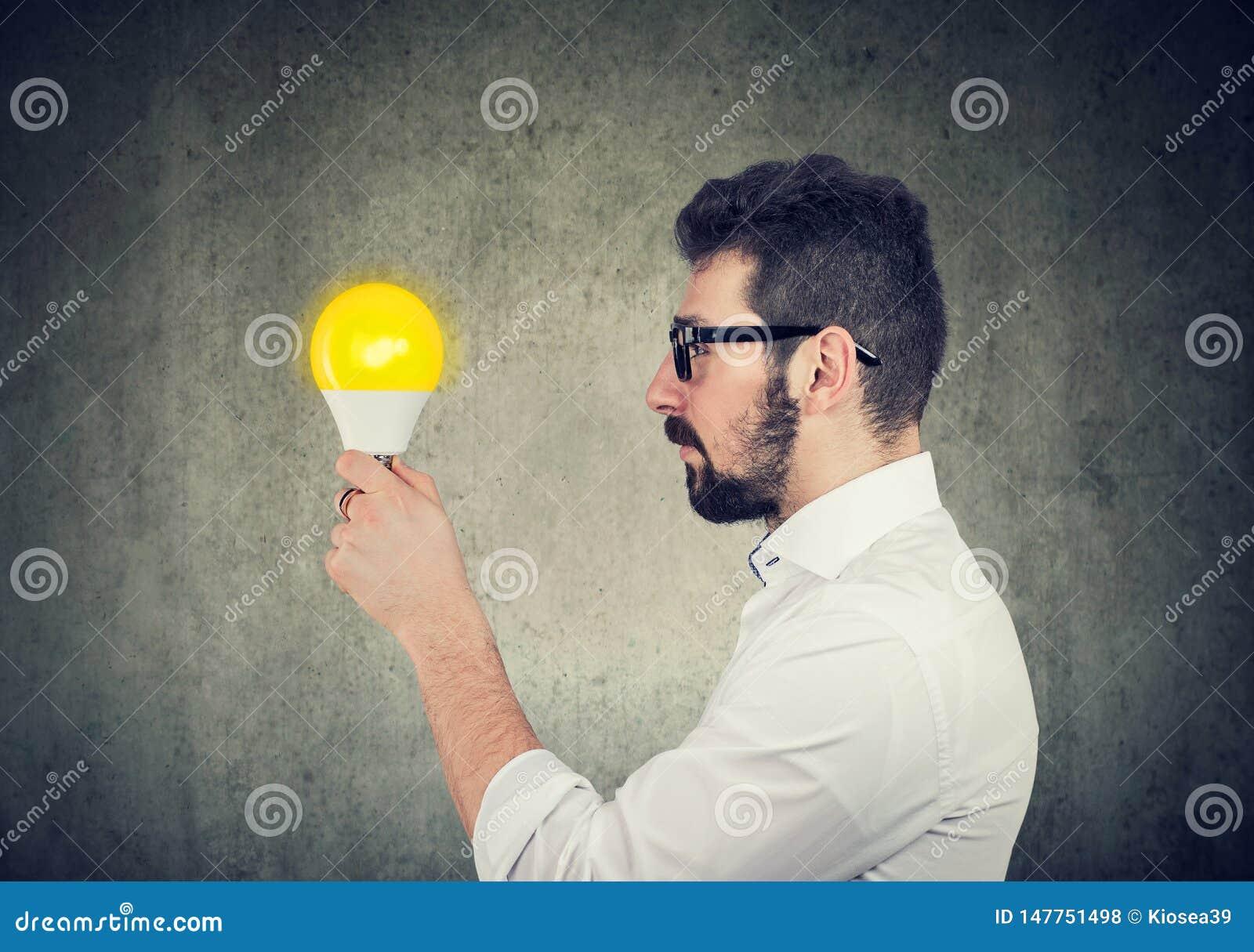 Hombre de negocios con la expresión pensativa que mira la bombilla brillante