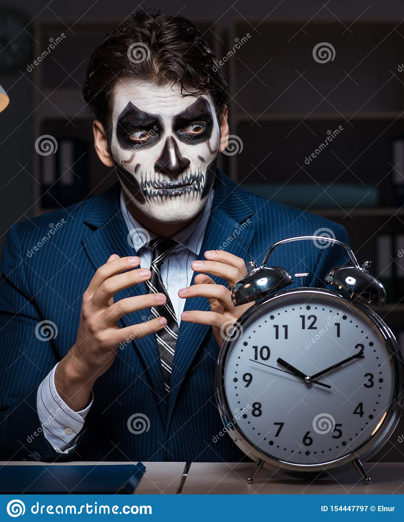 Hombre de negocios con la mascarilla asustadiza que trabaja tarde en oficina