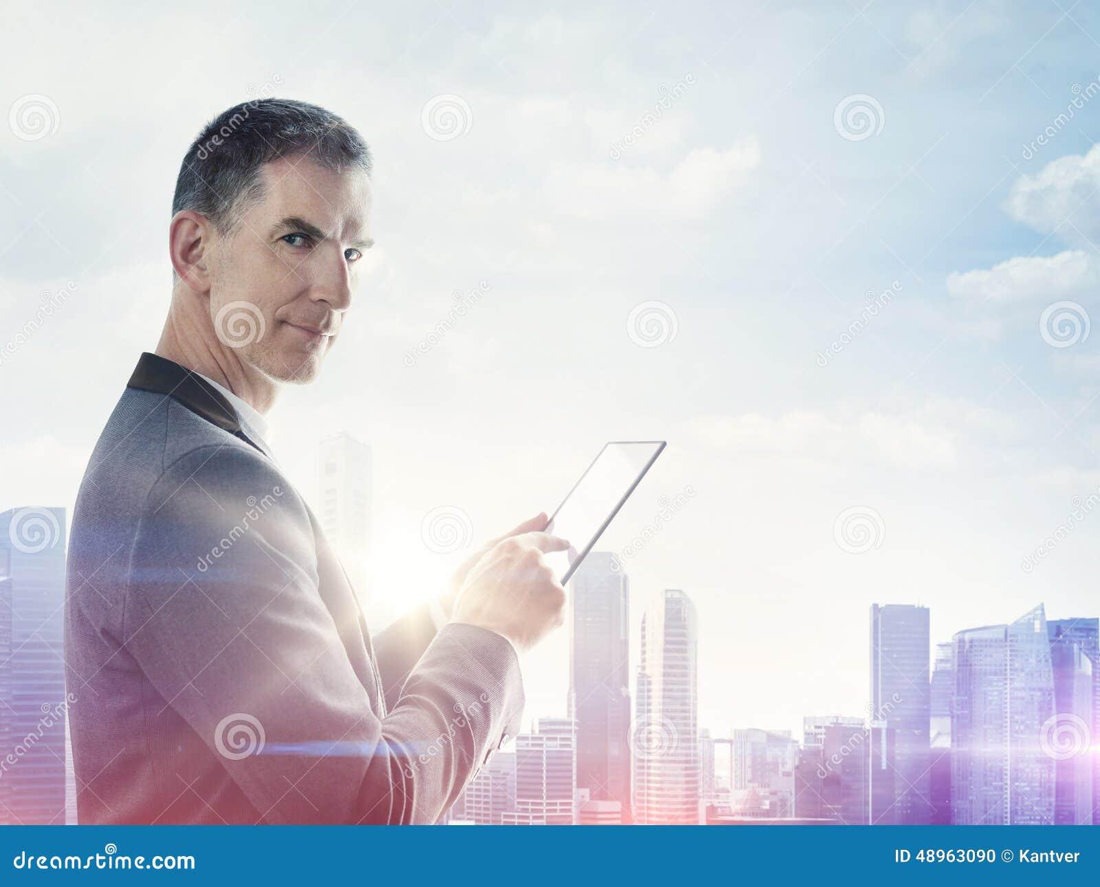 Hombre de negocios con la tableta digital y ciudad borrosa en horizonte