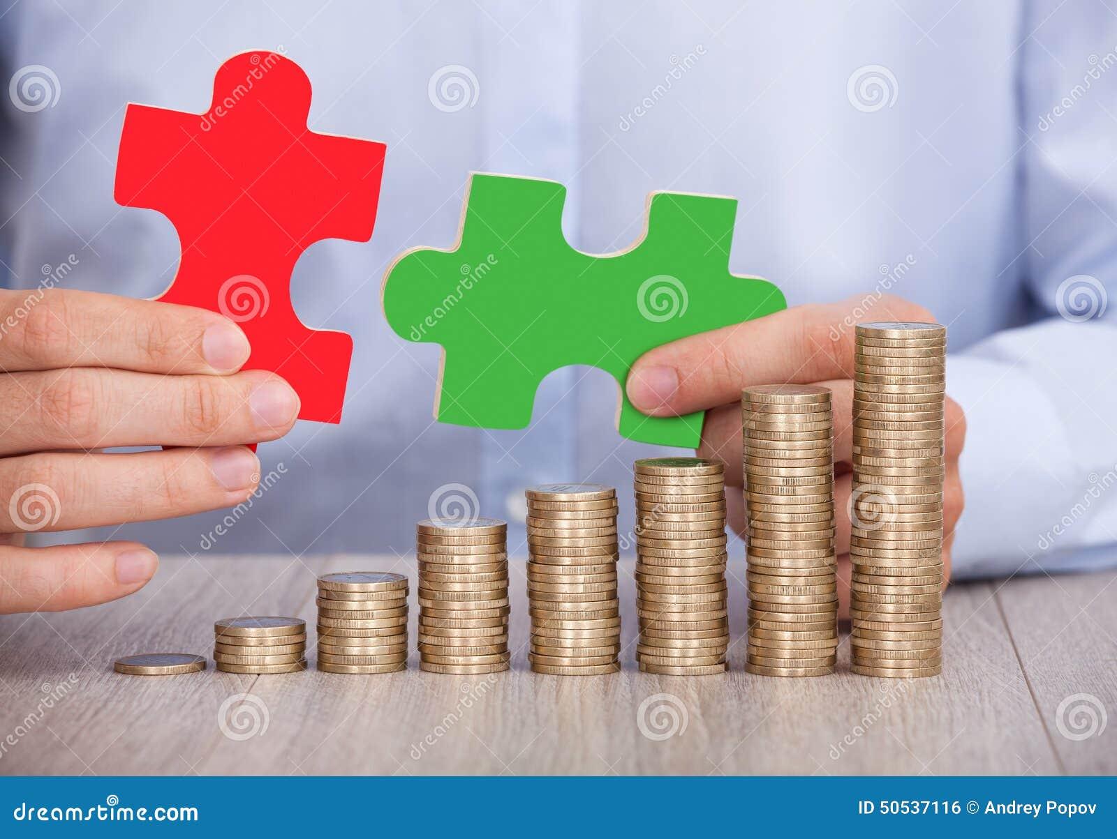 Hombre de negocios con los pedazos del rompecabezas y las monedas apiladas en el escritorio