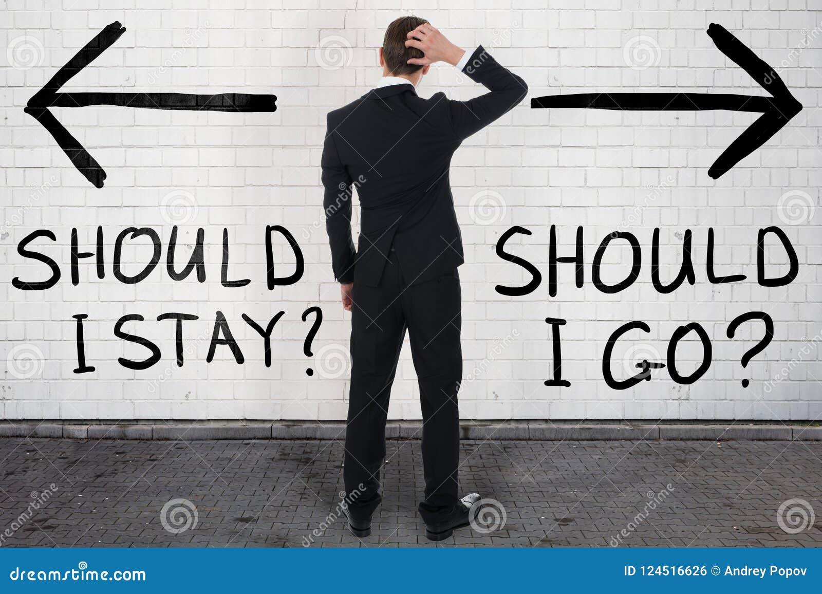 Hombre de negocios confuso Looking At Should que permanezco o que voy texto