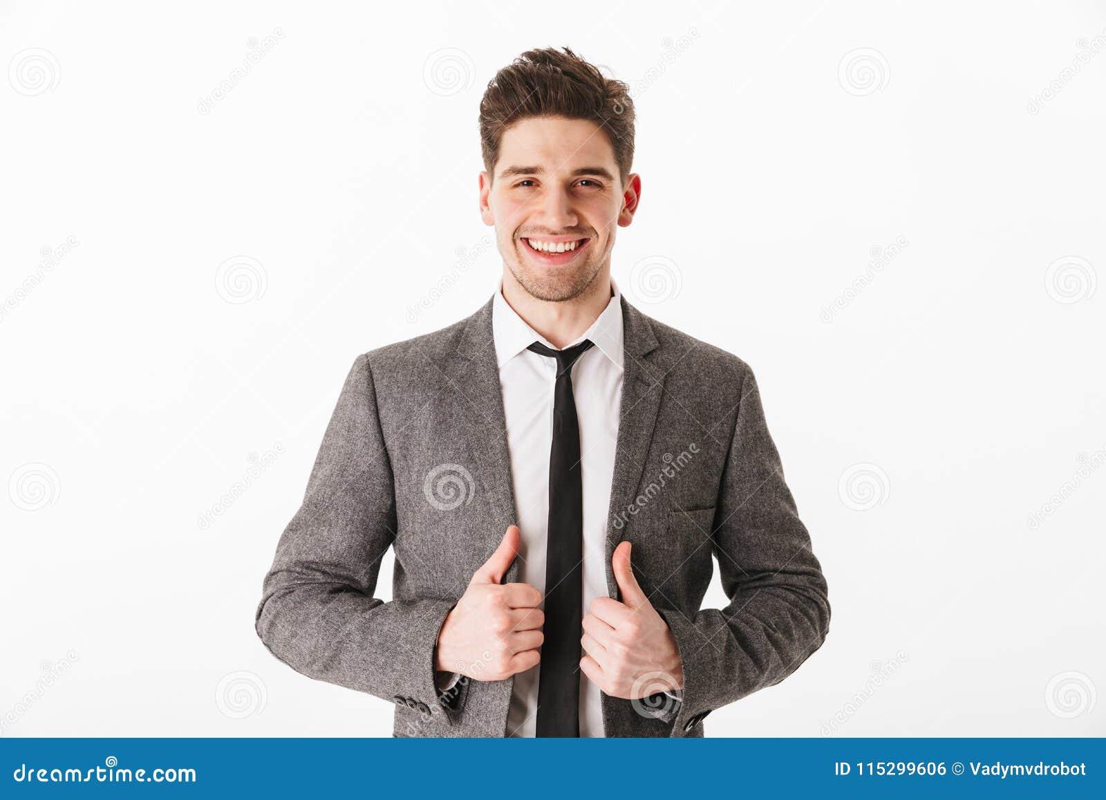 Hombre de negocios contento que sostiene la chaqueta y que mira la cámara