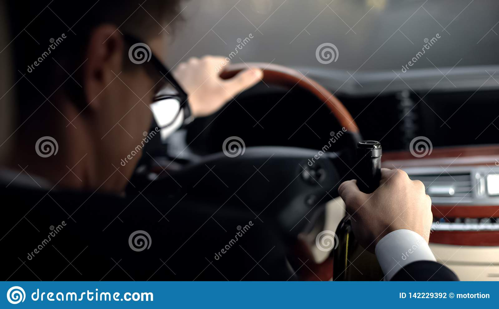 Hombre de negocios del trastorno que se sienta en coche con la botella de vino, conducción irresponsable, crisis