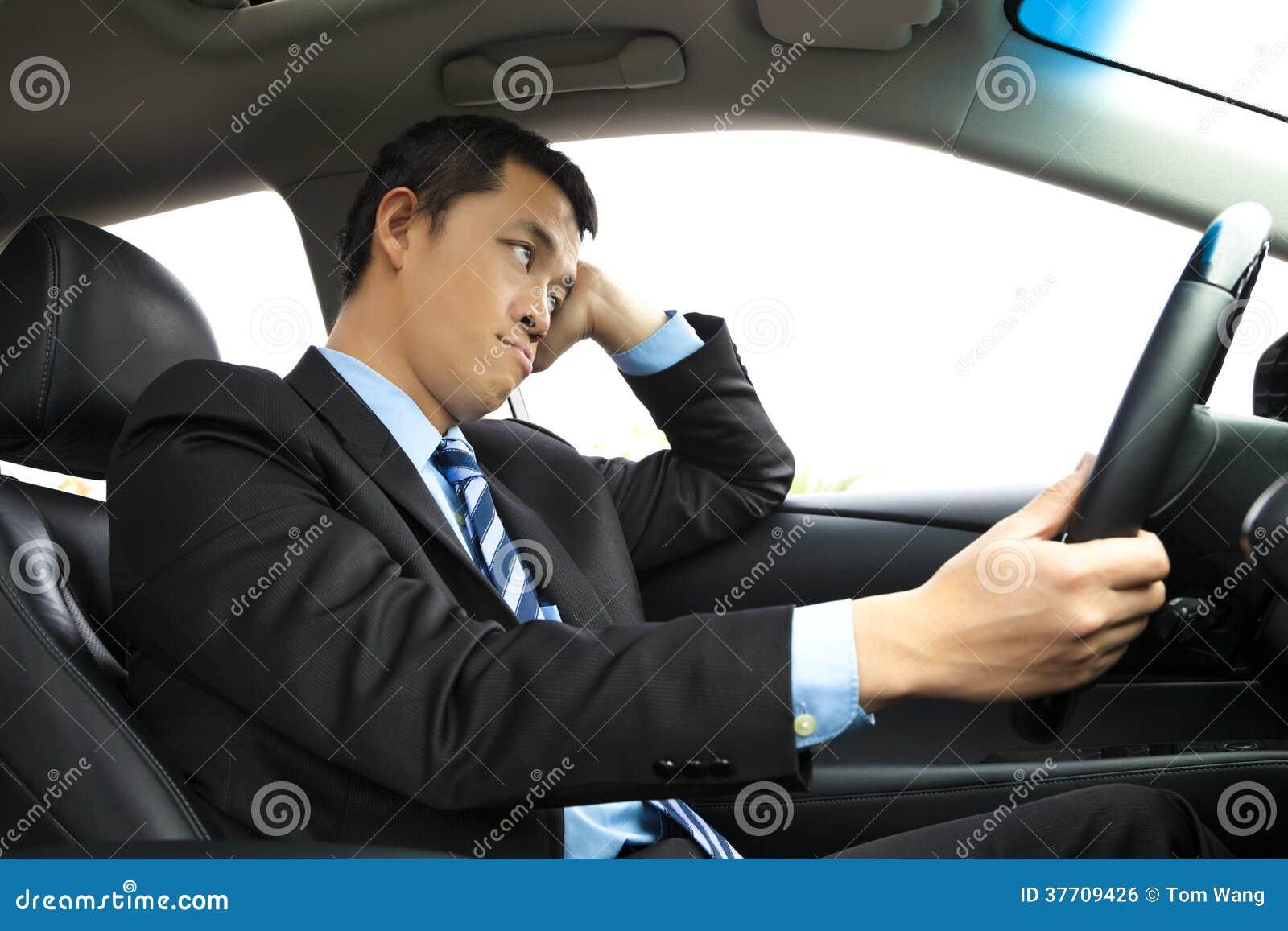 Hombre de negocios deprimido que se sostiene principal y que conduce el coche
