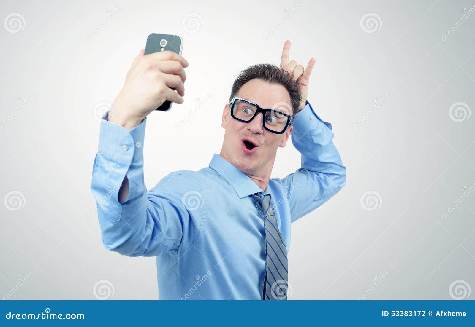 Hombre de negocios divertido que se fotografía en un smartphone